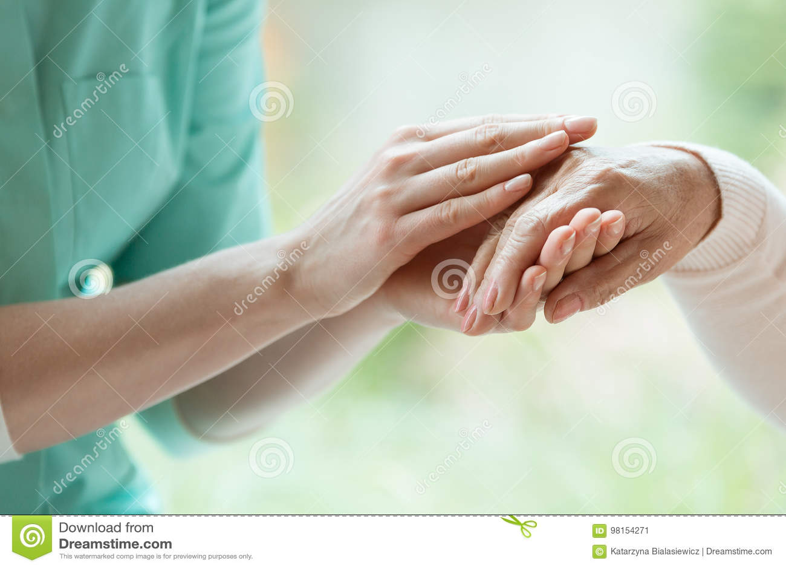 Caretaker massaging pensioner`s hand