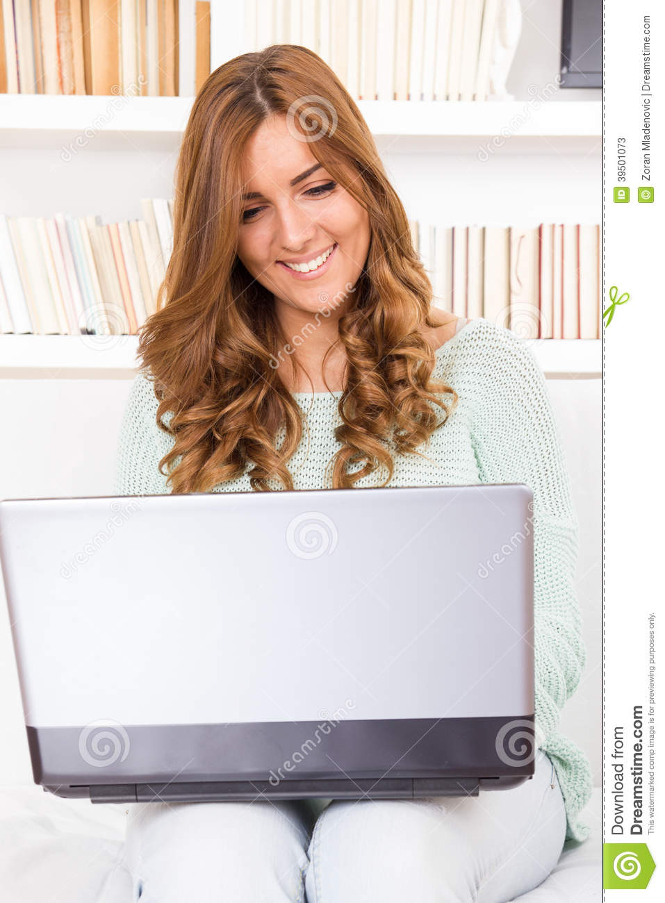 Young casual beautiful woman using a laptop computer at home