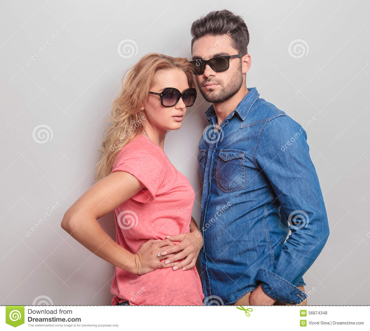 Young Casual Couple Posing, Both Wearing Sunglasses. Stock