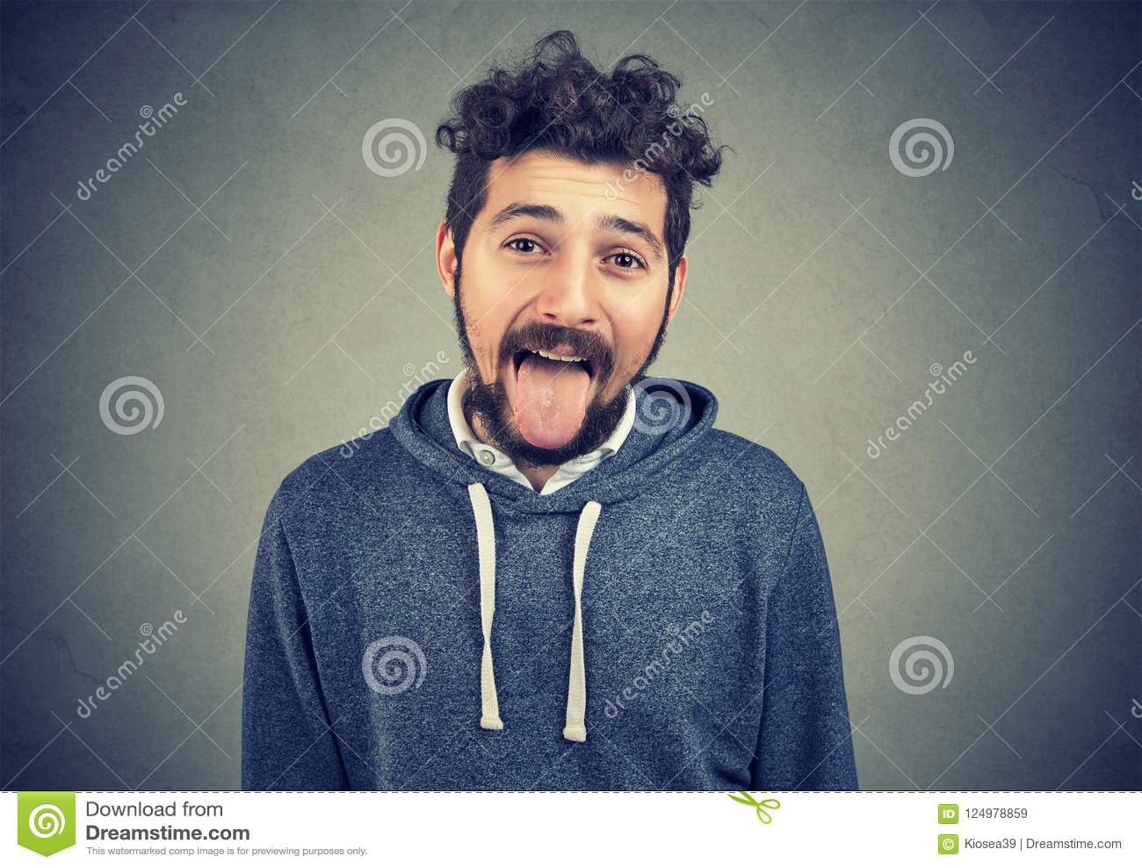 Childish Man Grimacing At Camera Sticking Out His Tongue