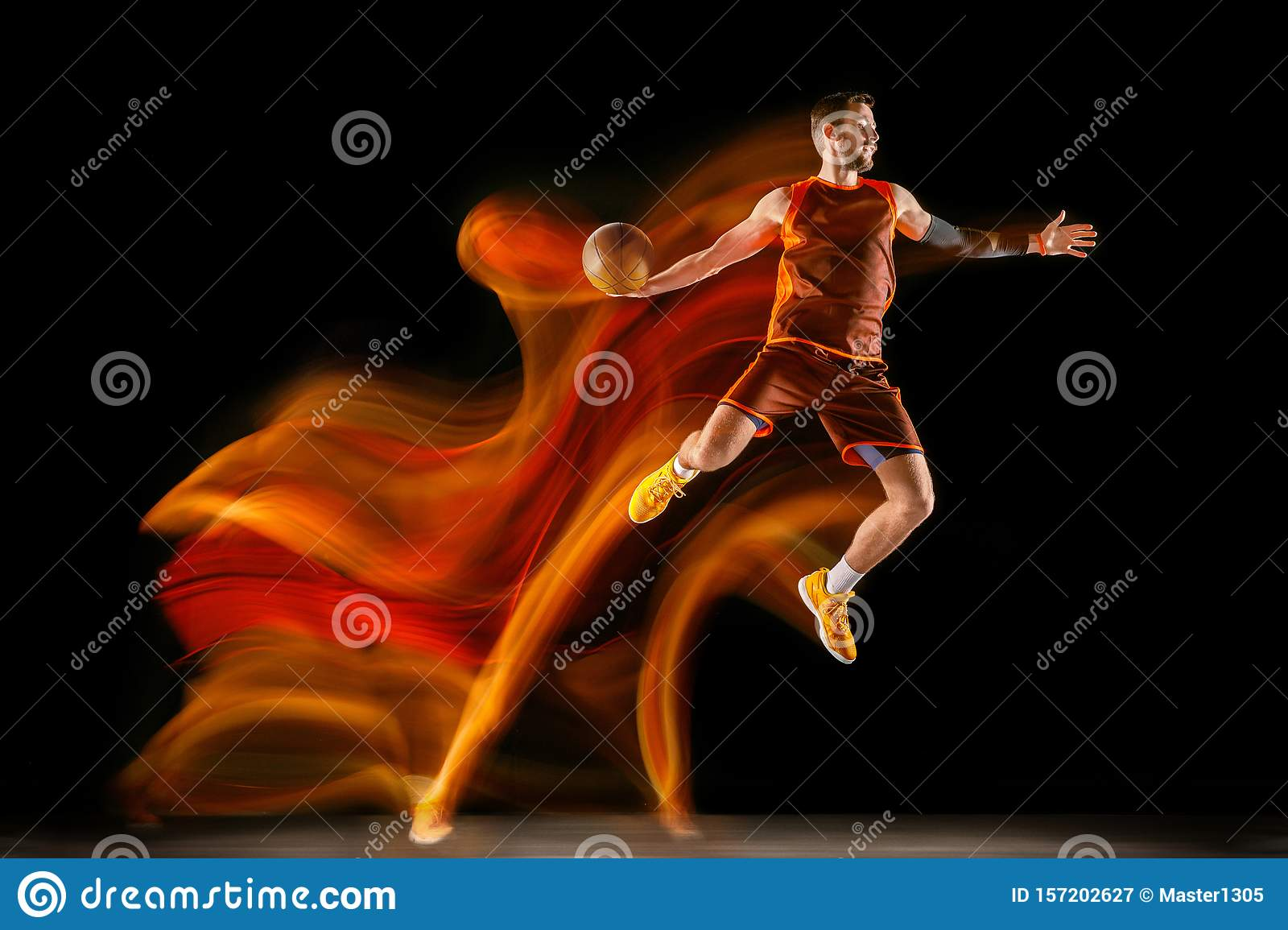 Young caucasian basketball player against dark background in mixed light