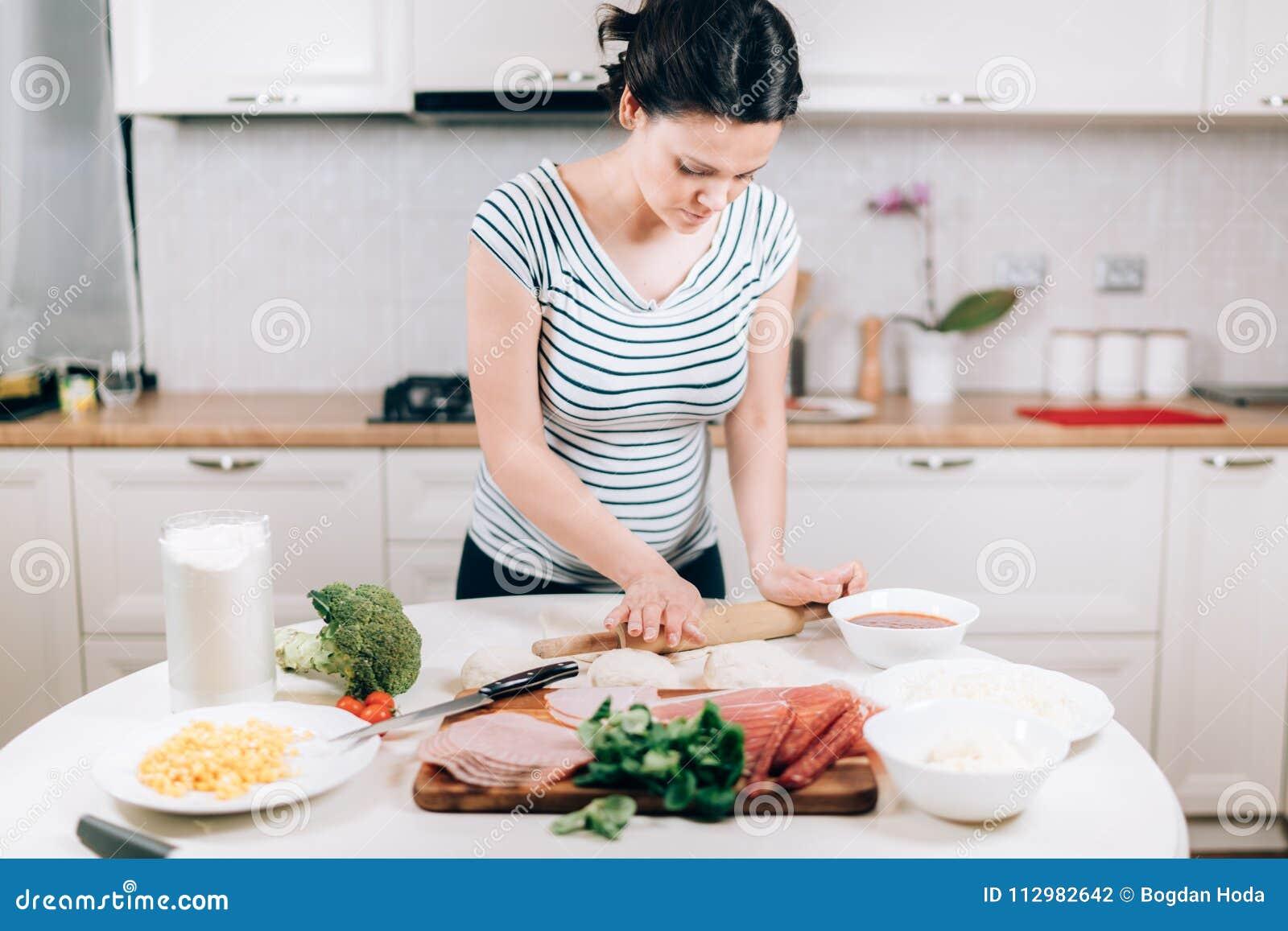 Young caucasian, beautiful pregnant woman preparing dough for pizza