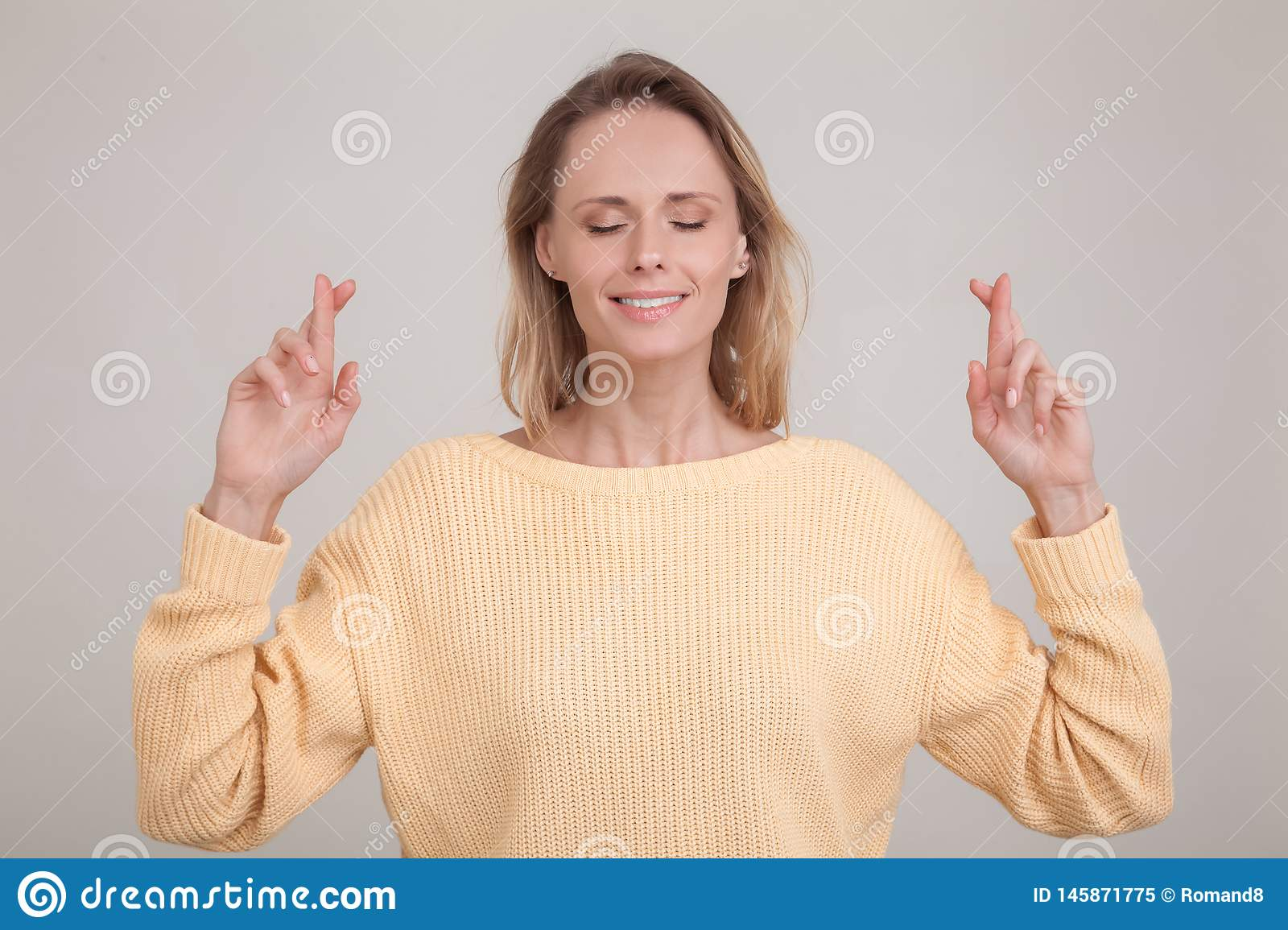 Young caucasian blonde female closing her eyes crossing fingers with hope, anticipating important news.wearing yellow sweater.