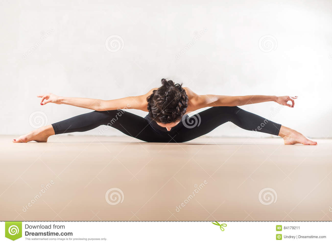 Young Caucasian dancer doing seated wide leg forward bend exercise stretching spine and legs