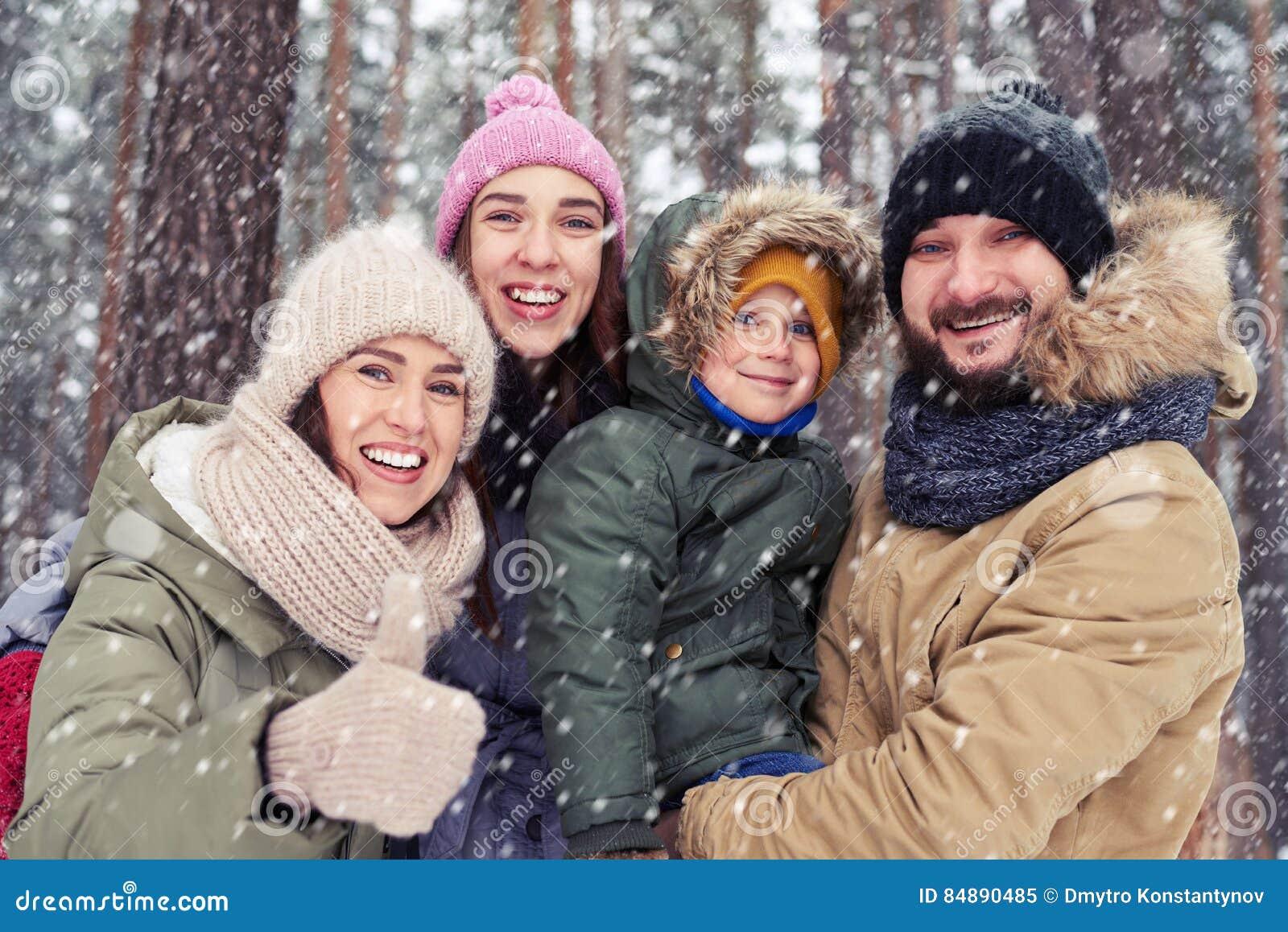 Young Caucasian family smiling waving to camera and having fun o