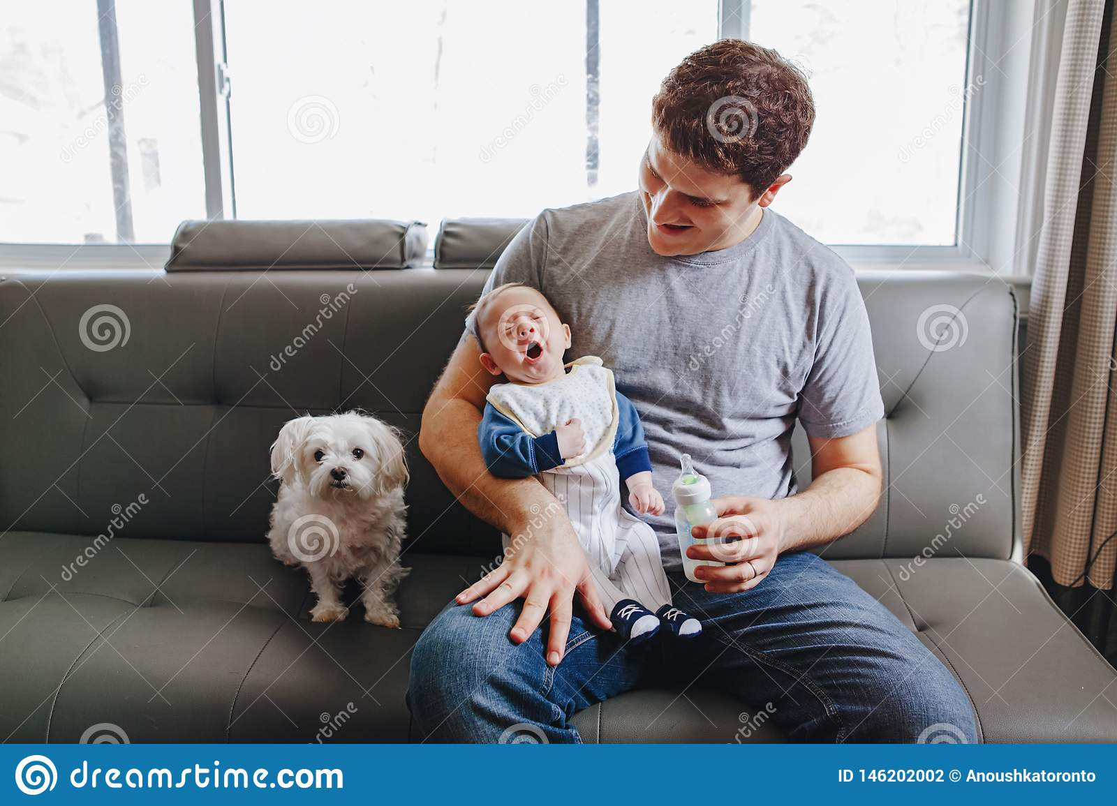 Young Caucasian father playing with newborn baby.