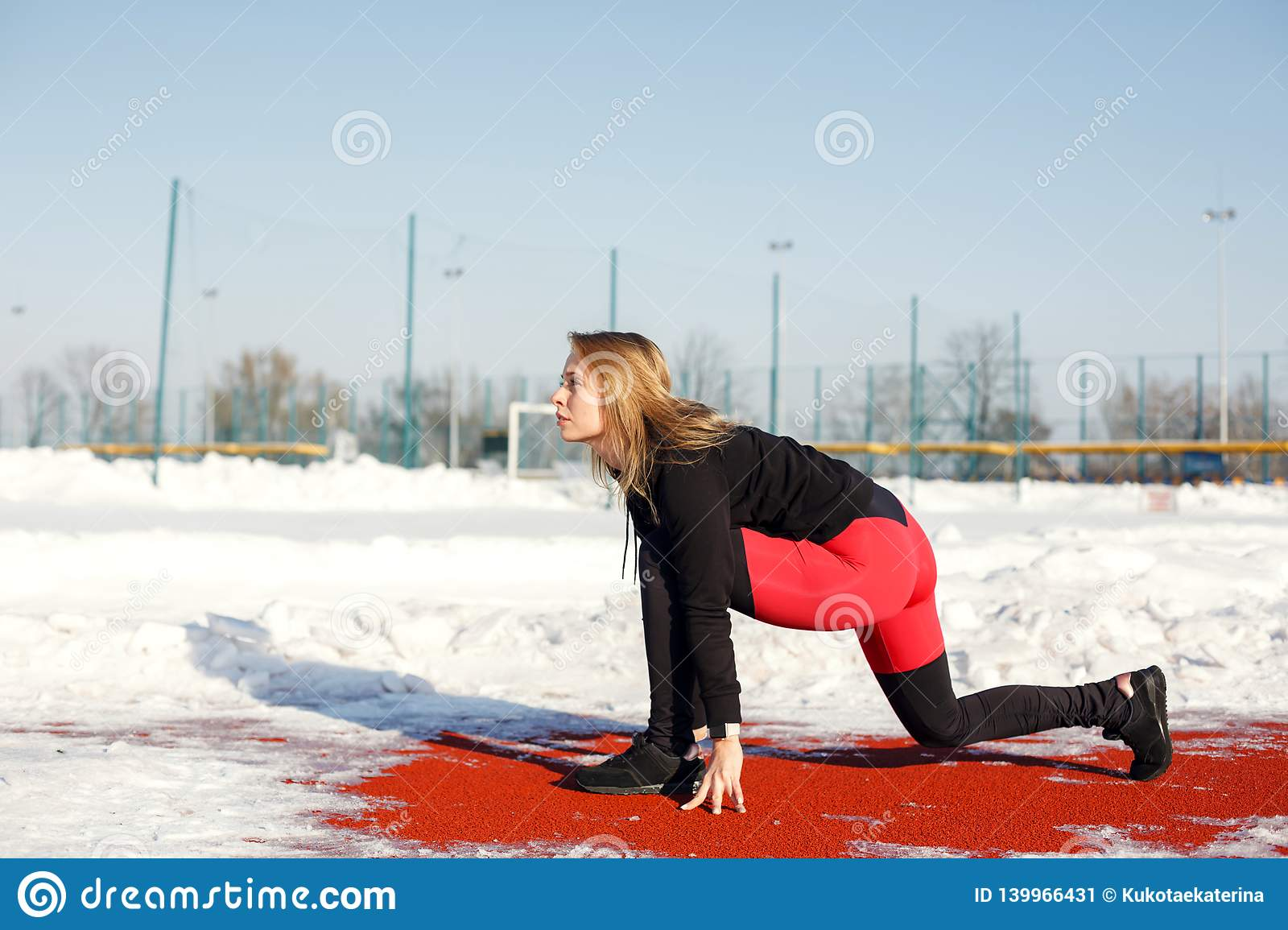 Young caucasian female blonde in red leggings stretching exercise on a red running track in a snowy stadium. fit and sports