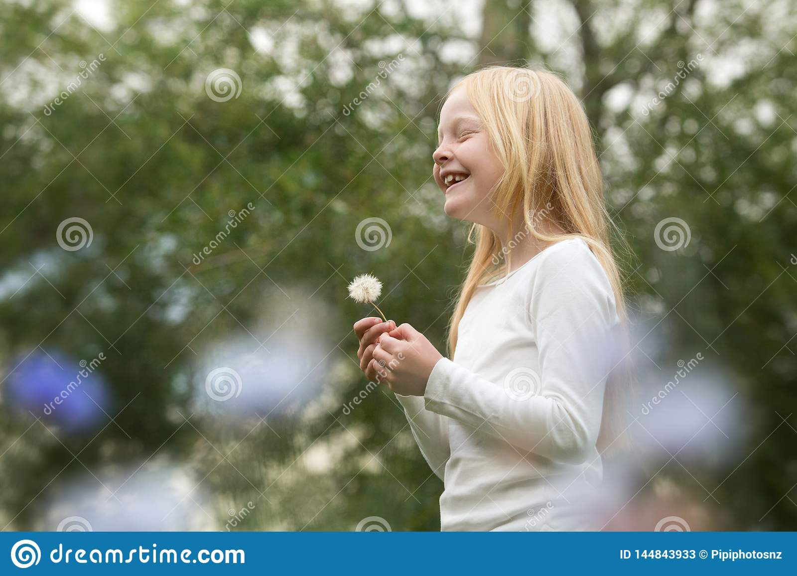 Young caucasian girl wishes on a dandelion