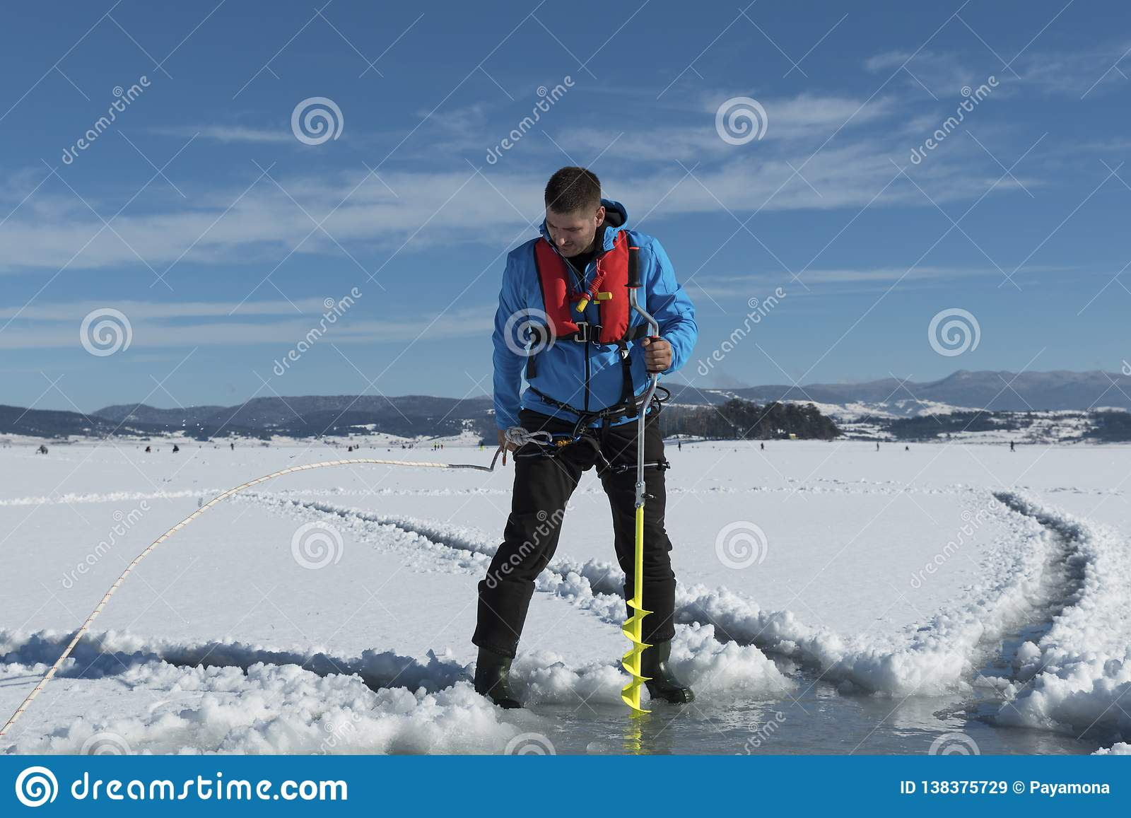 Young Caucasian man drilling ice on a frozen lake with yellow ice auger drill wearing life vest. Selective focus