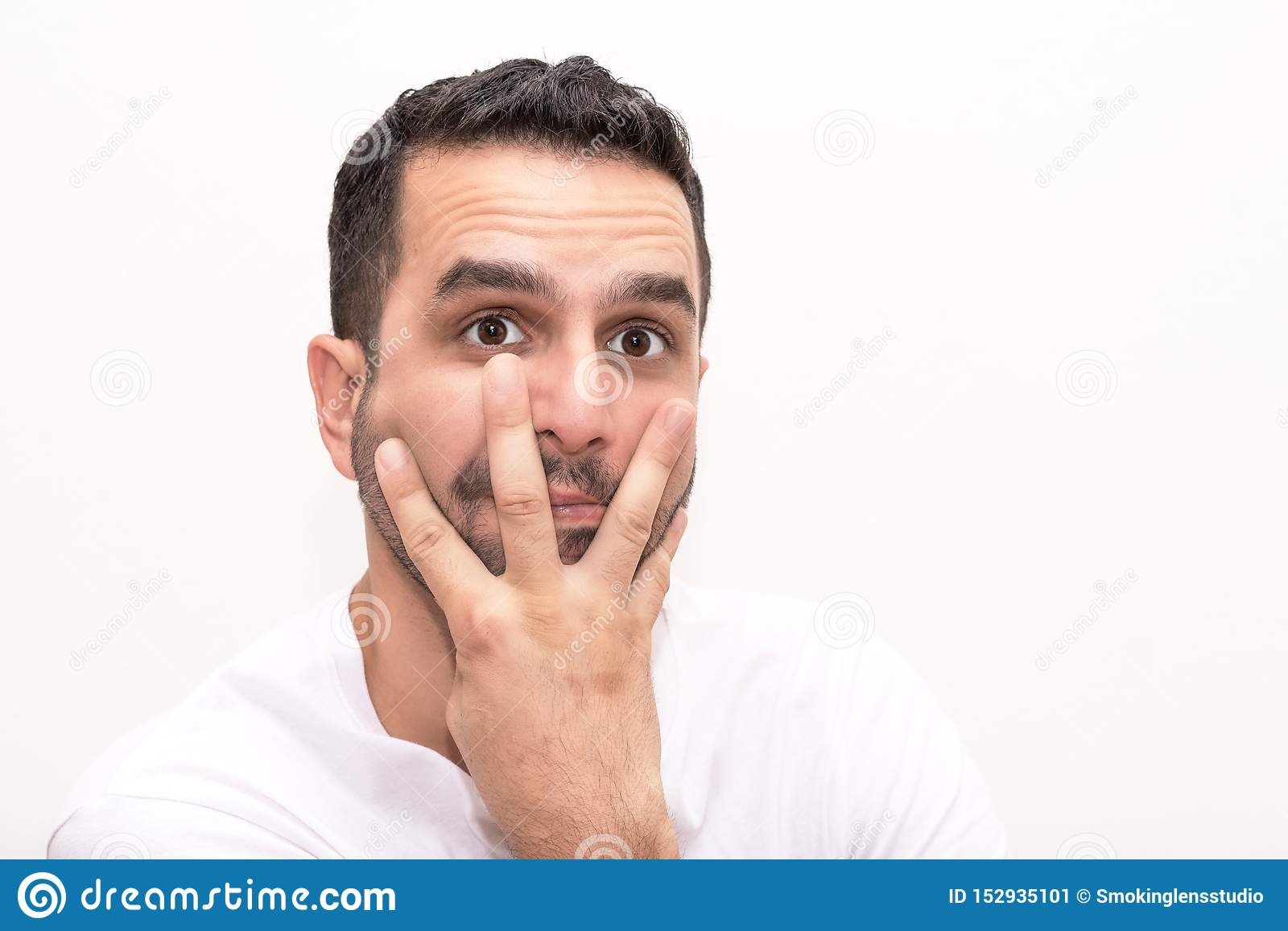 Young Caucasian man eith fingers on face
