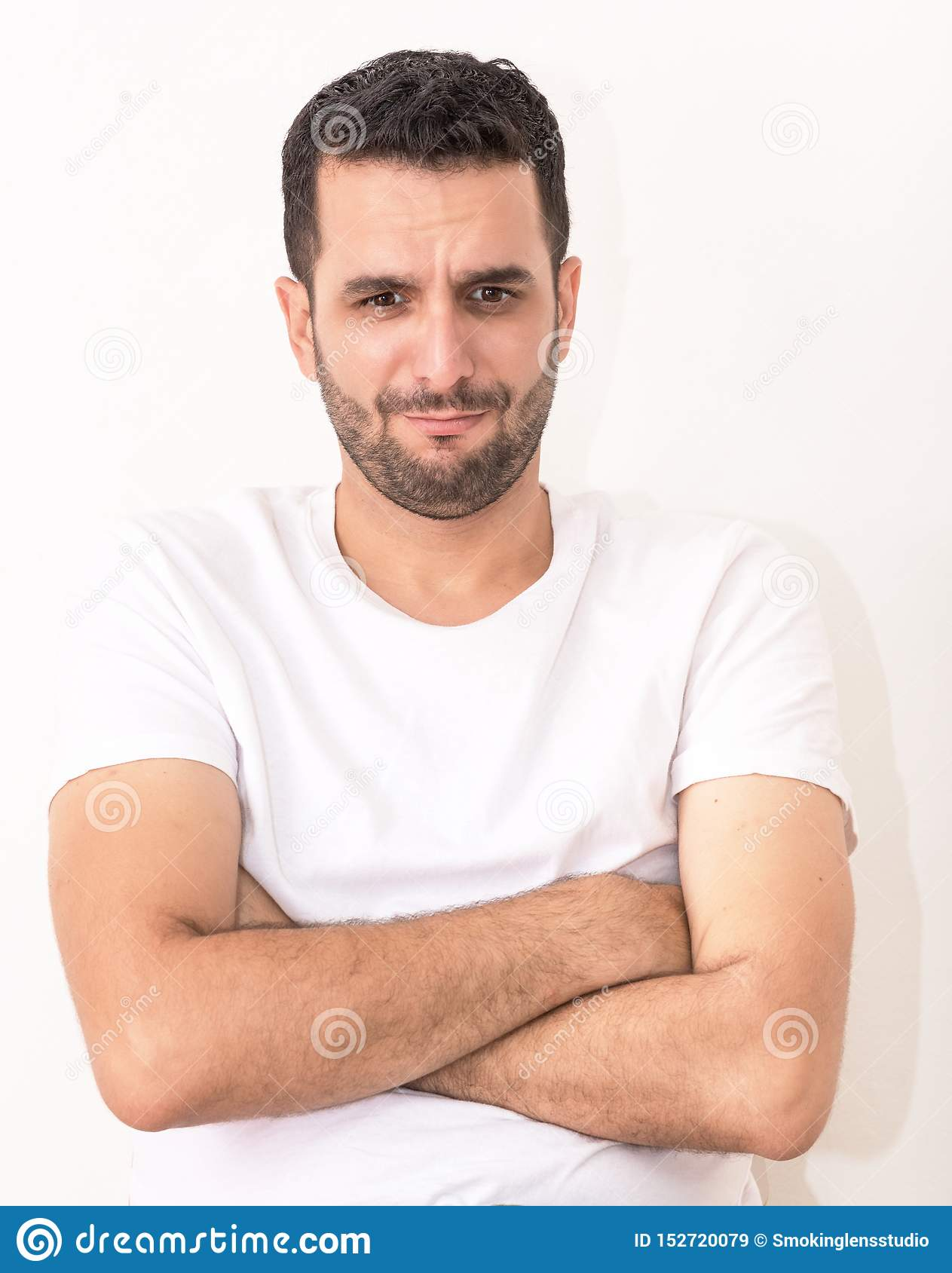 Young caucasian man with his hands crossed, he looks hurt and sad