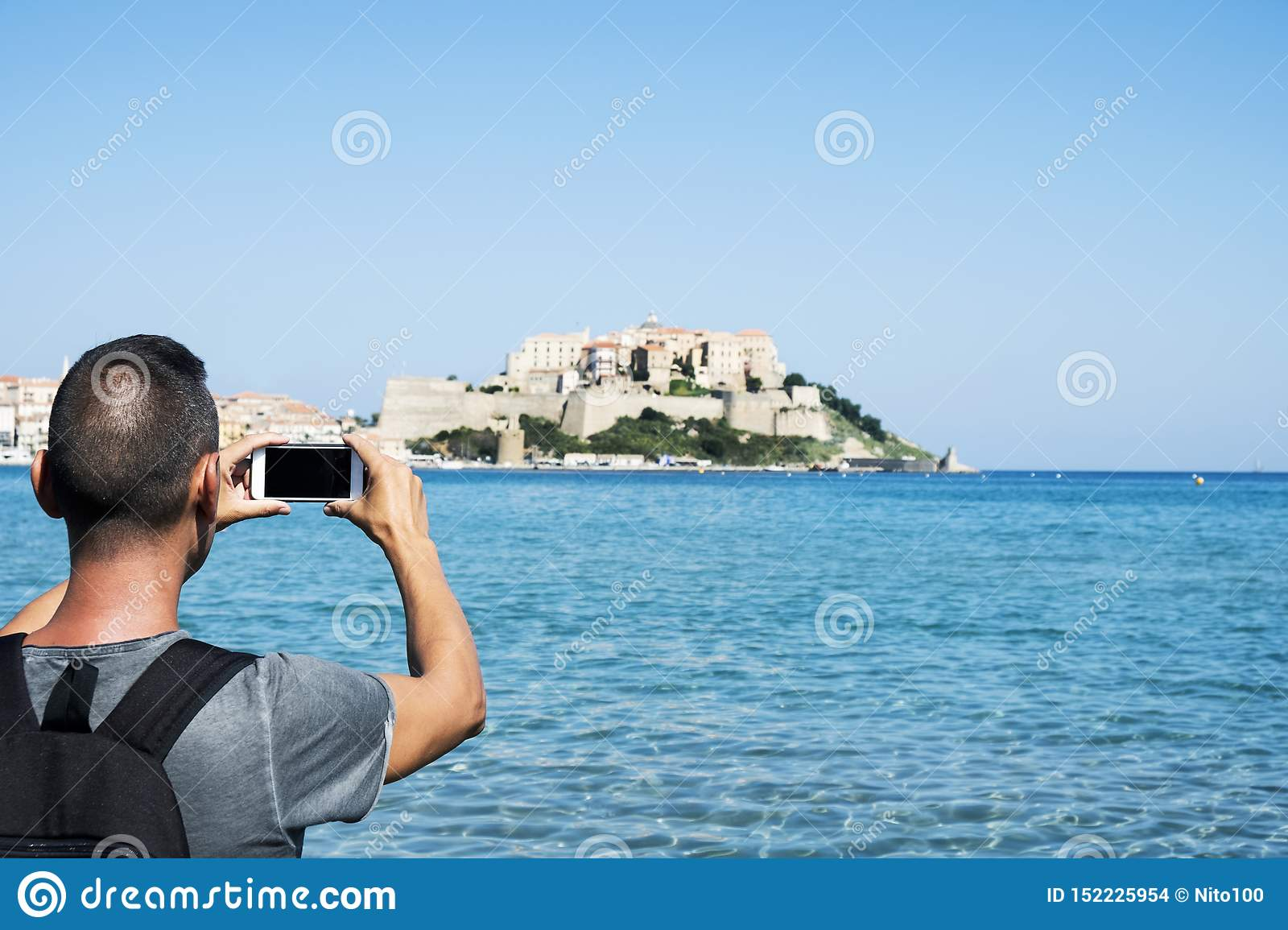 Man taking a picture of Calvi, in Corsica, France