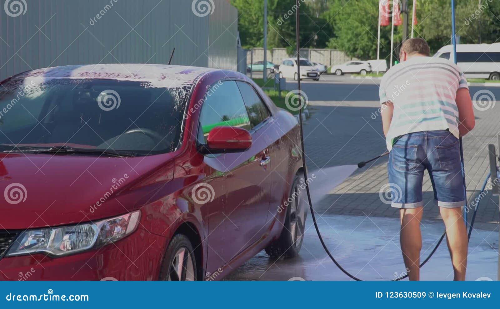 Young caucasian man washing his car on the car wash self-service  Car  washing  Automotive, nozzle