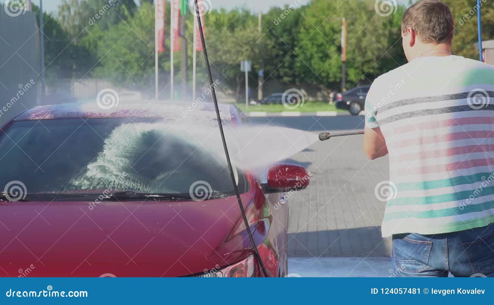 Young caucasian man washing his car on the car wash self-service  Car  washing  Garage, nozzle
