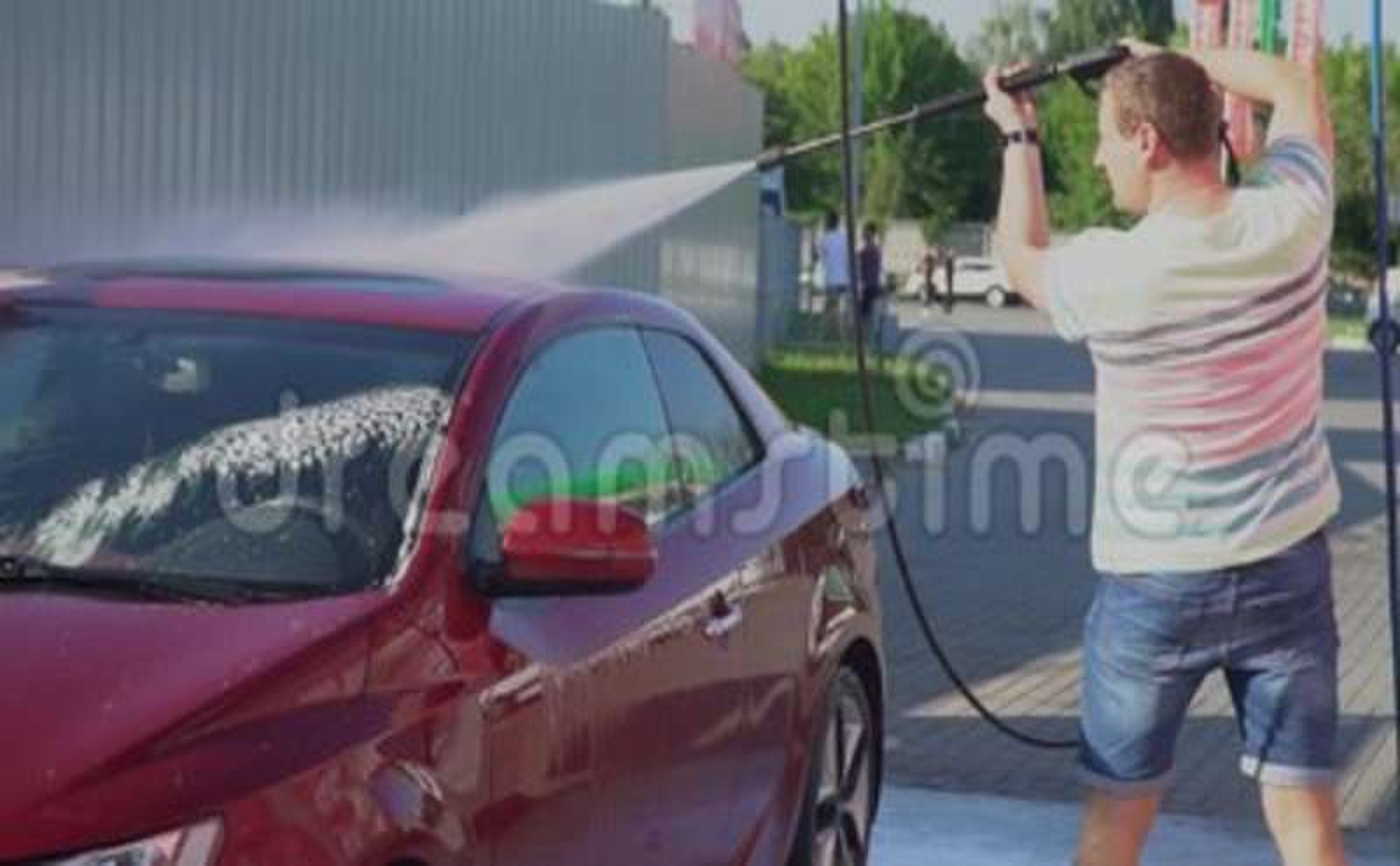 Young caucasian man washing his car on the car wash self-service  Car  washing  Foam, automotive