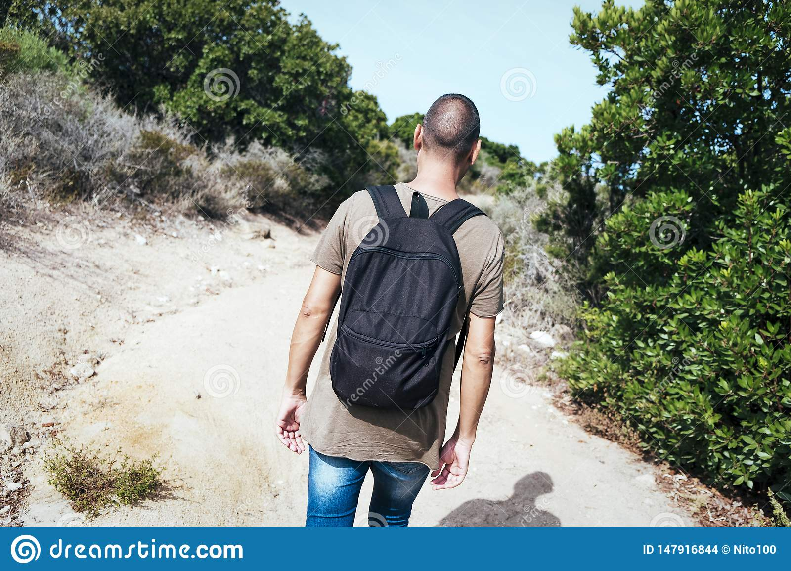 Man carrying a backpack walking by a dirt road