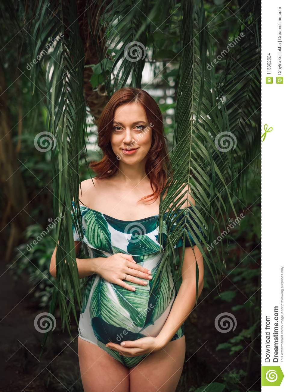 ff1c9dd7e7d0d Attractive soon to be mom with a natural beauty and long red hair wearing  floral swimsuit posing among palm leaves at tropical forest, caressing her  belly ...