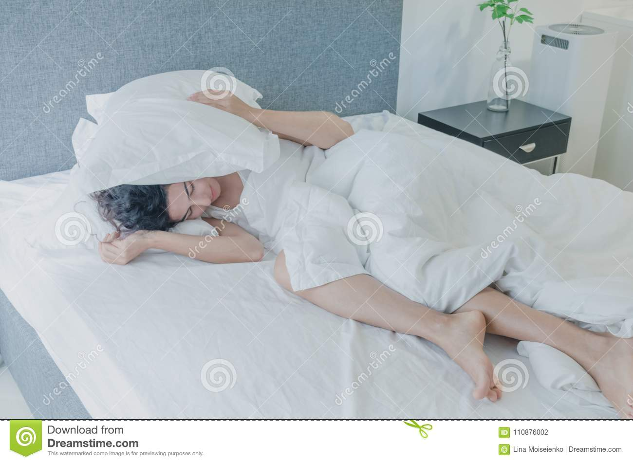 Young caucasian woman with black hair sleeps funny in bed, covering her head with pillow.