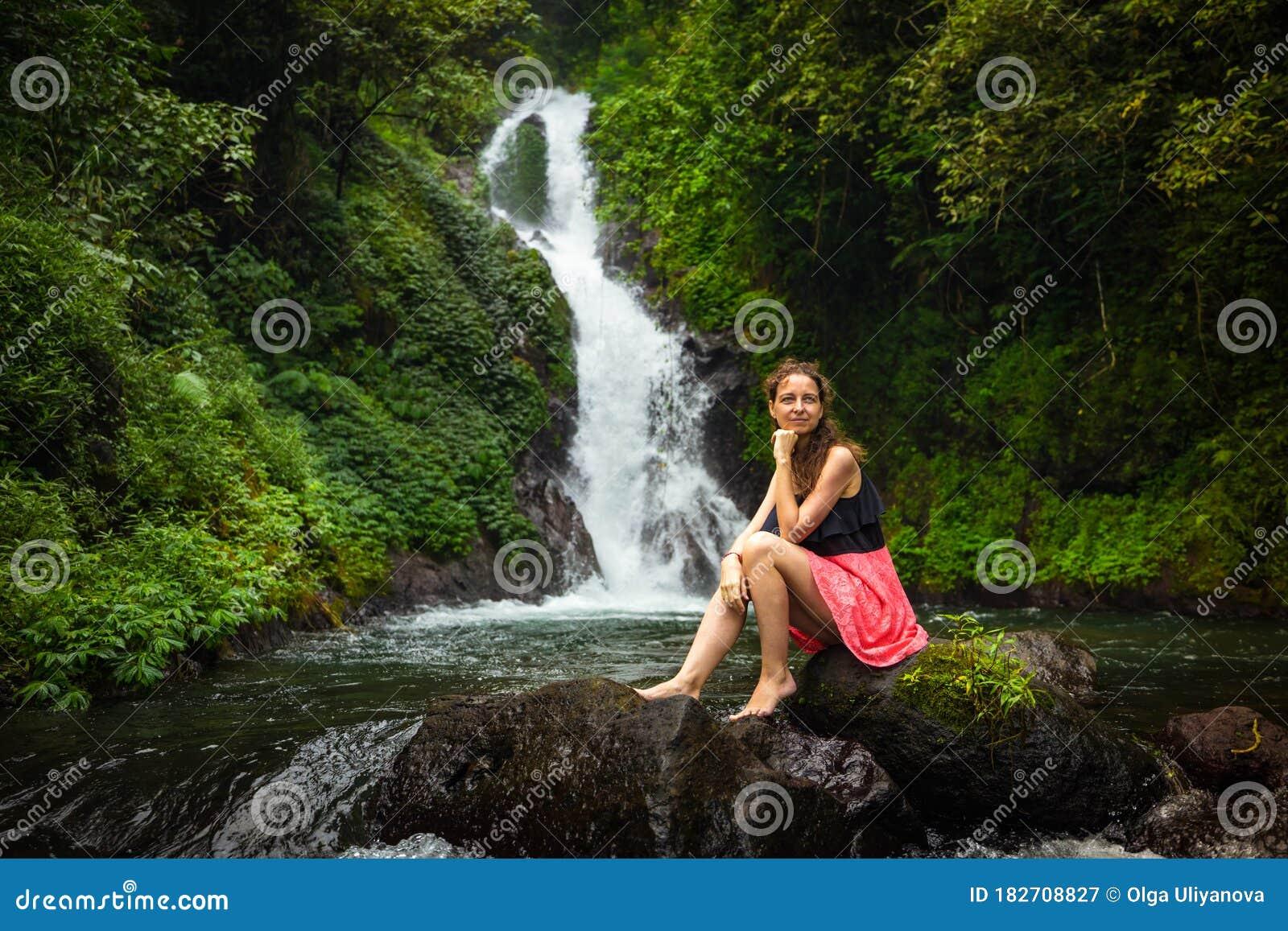 Dutch Woman Sitting On Rock Near Waterfall Stock Image
