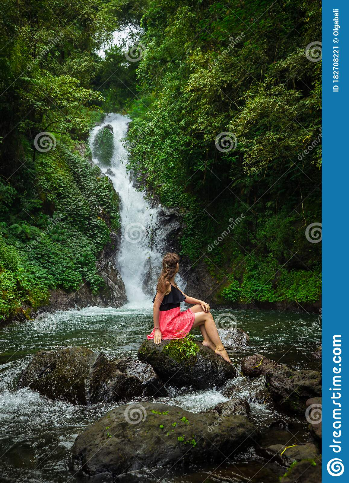 girl-sitting-in-the-landscape-besides-a-waterfall image