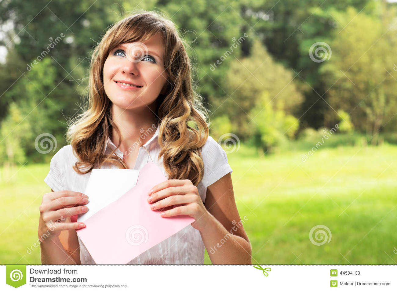 Young caucasian woman standing on blurred green summer background. Holding a blank letter in pink envelope. Letter and envelope co