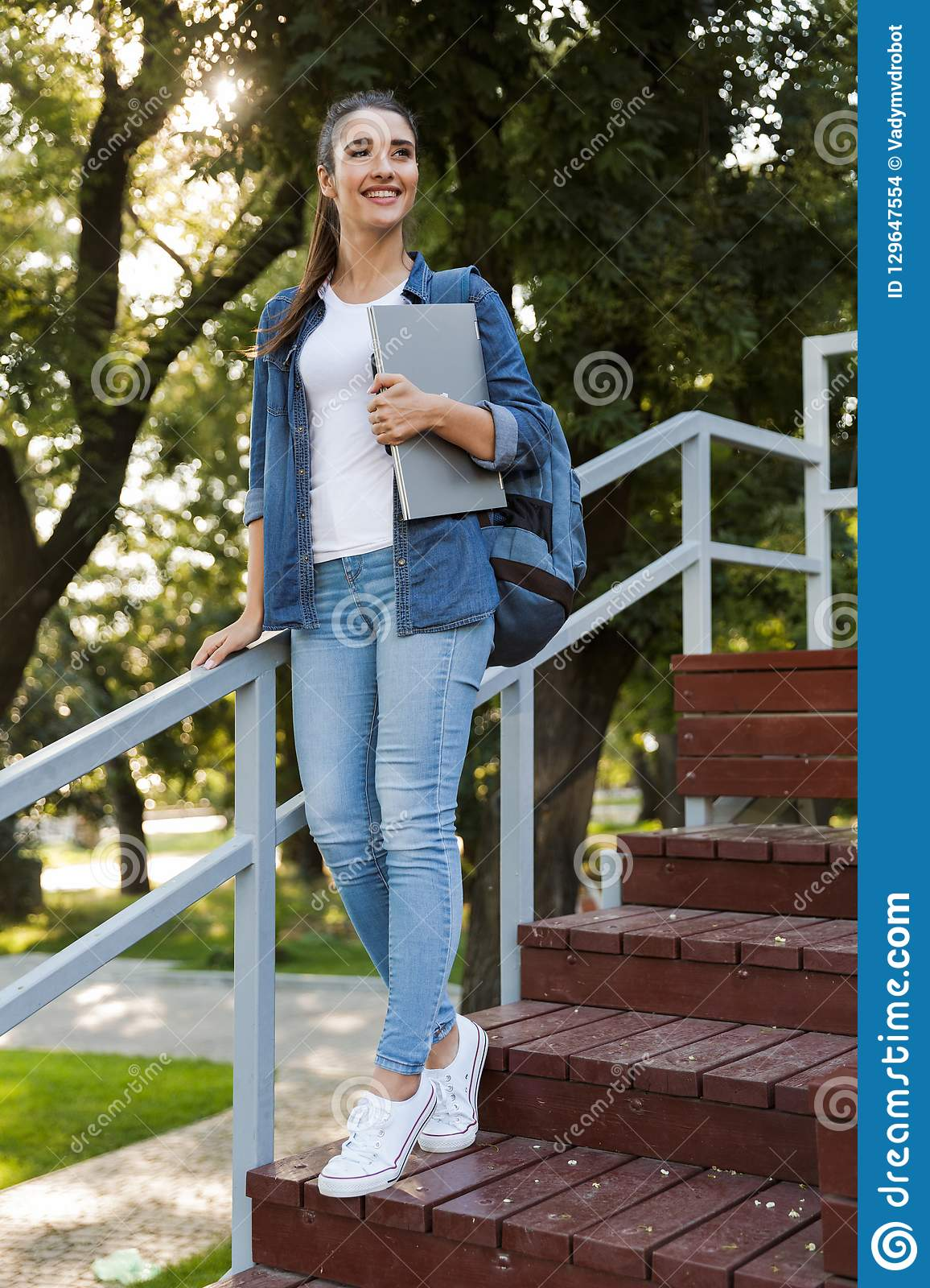Young caucasian woman standing outdoors holding laptop computer.