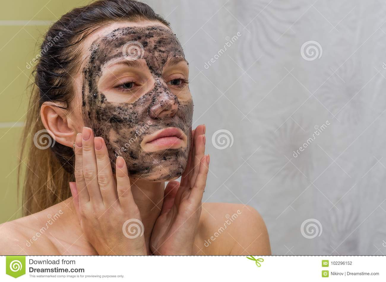 Young charming girl makes a black charcoal mask on her face
