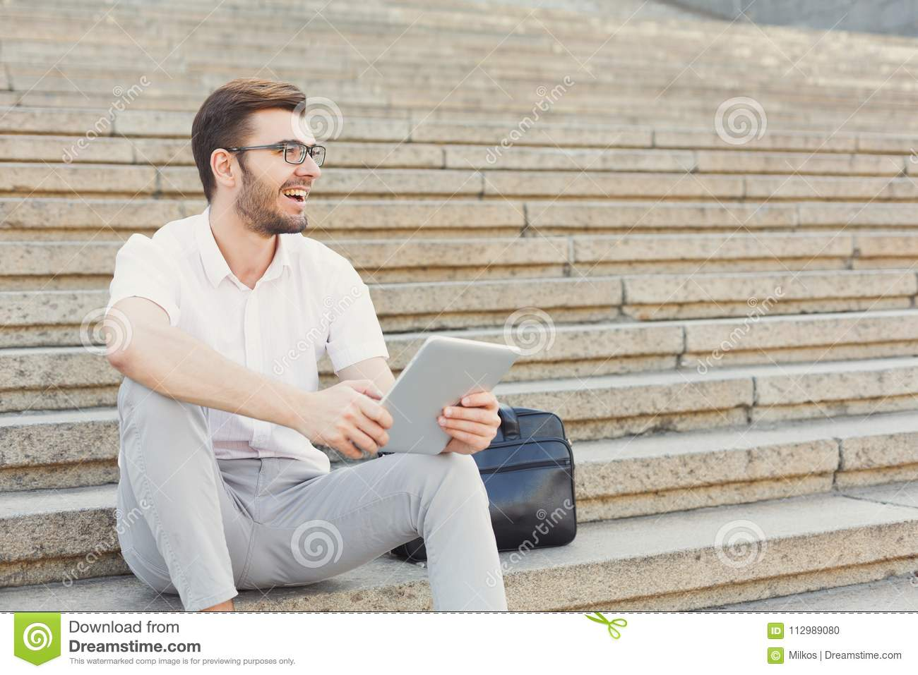 Young cheerful businessman using tablet outdoors