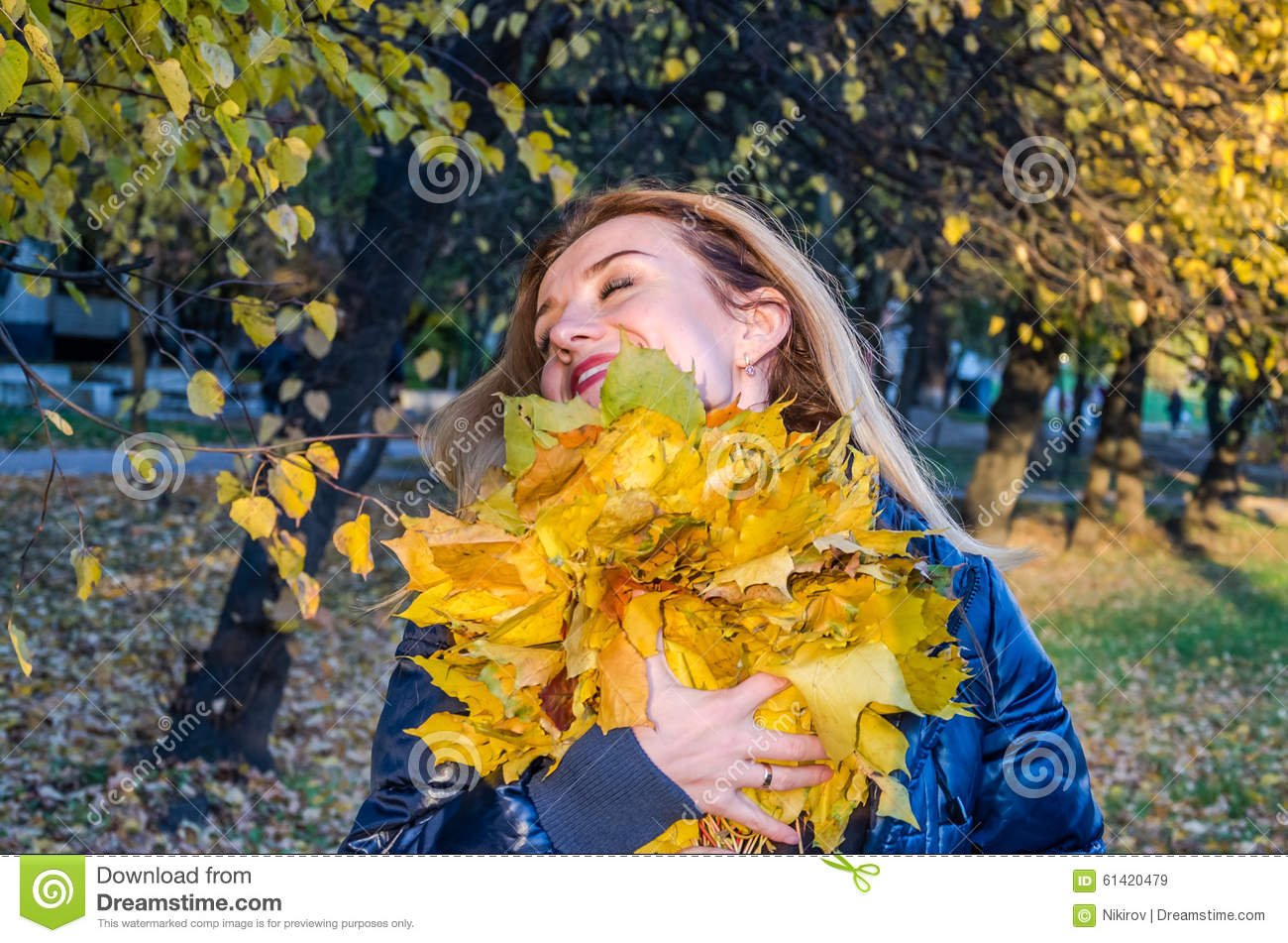 Young cheerful cute girl woman playing with fallen autumn yellow leaves in the park near the tree, laughing and smiling