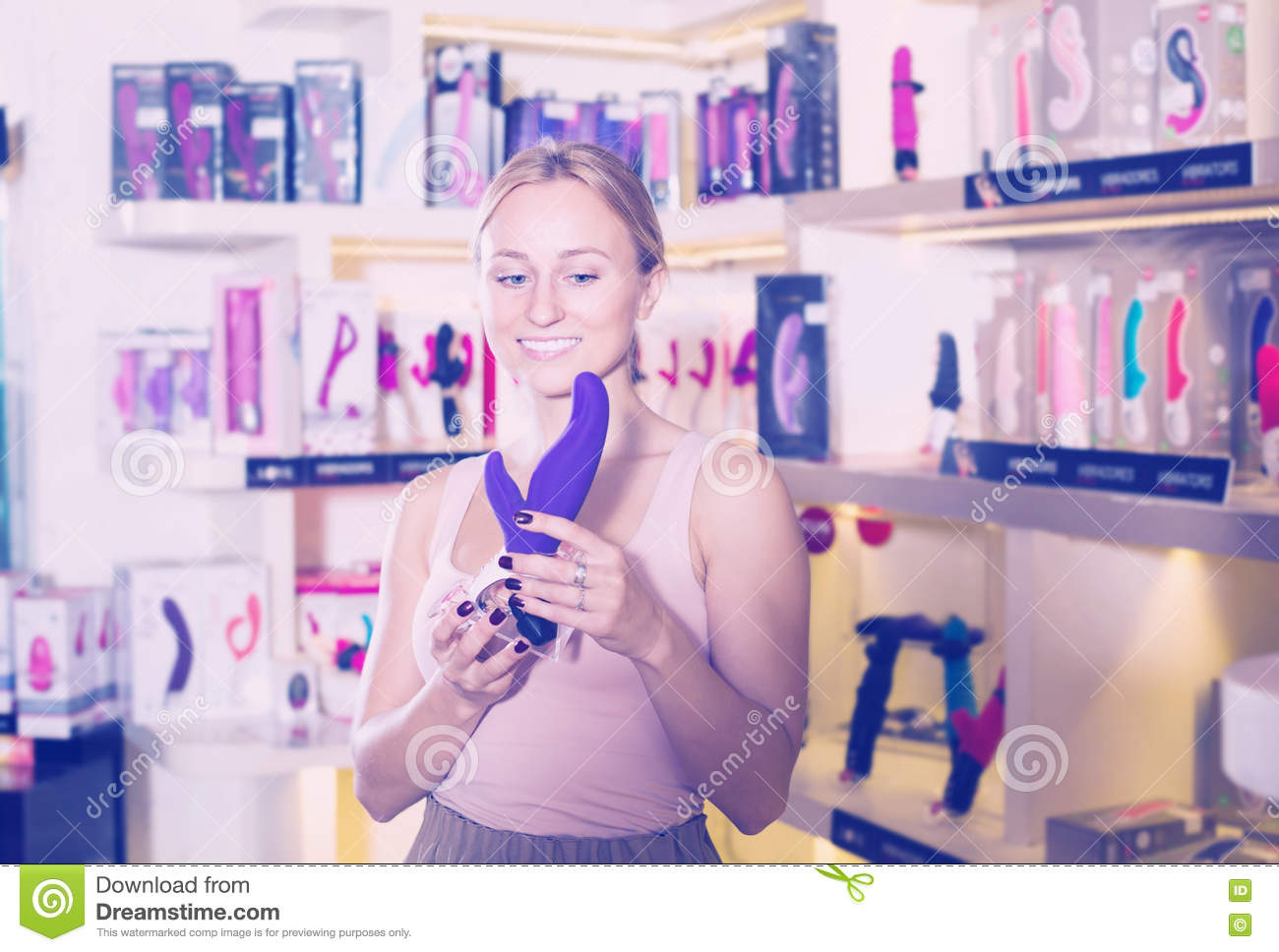 Young cheerful female buying sex toys in shop