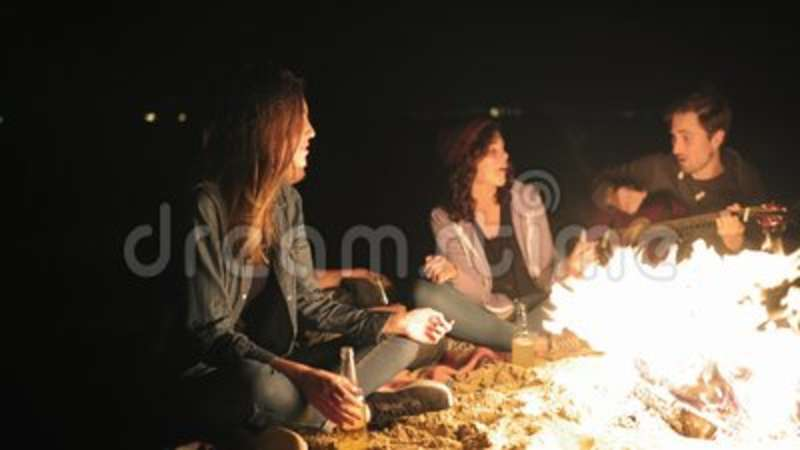 Young cheerful people sitting by the bonfire late at night, playing guitar,  singing songs and drinking beer  Cheerful