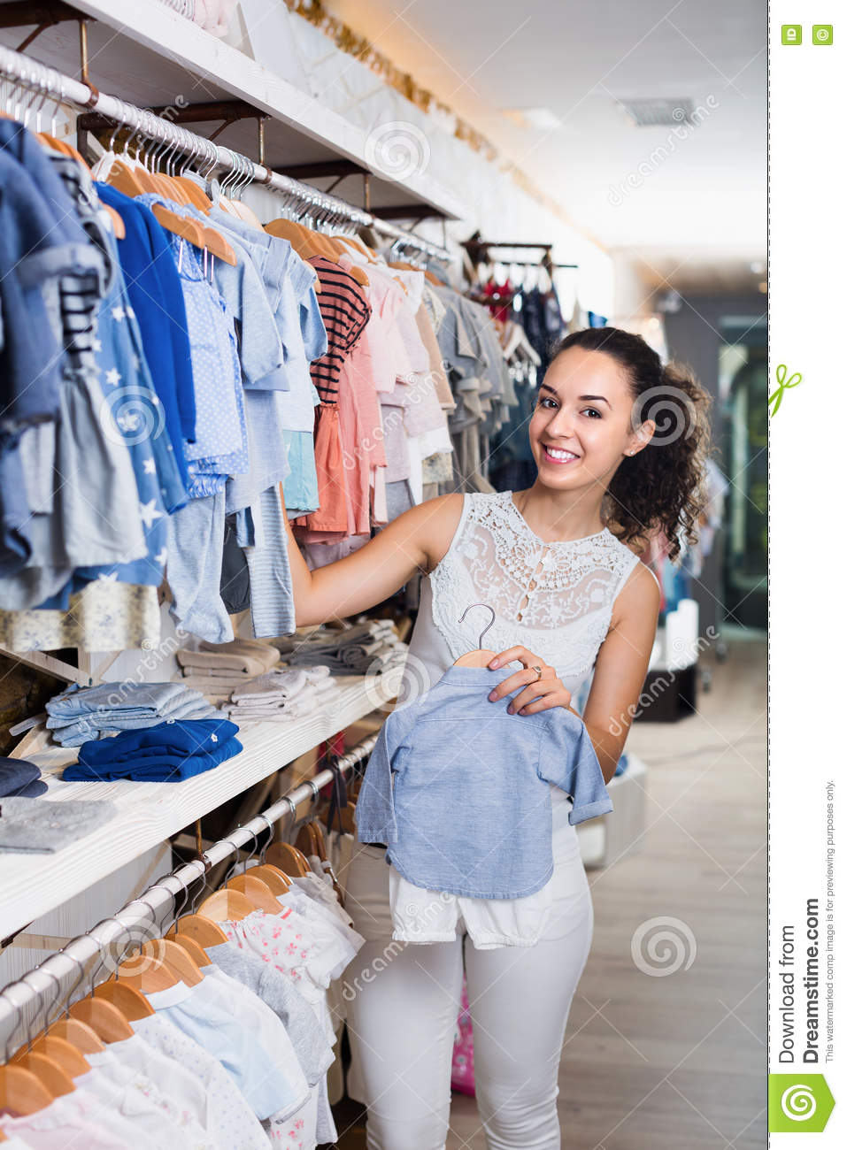 68009a7a2e Young cheerful woman holding blue baby clothes in kids apparel boutique.  More similar stock images