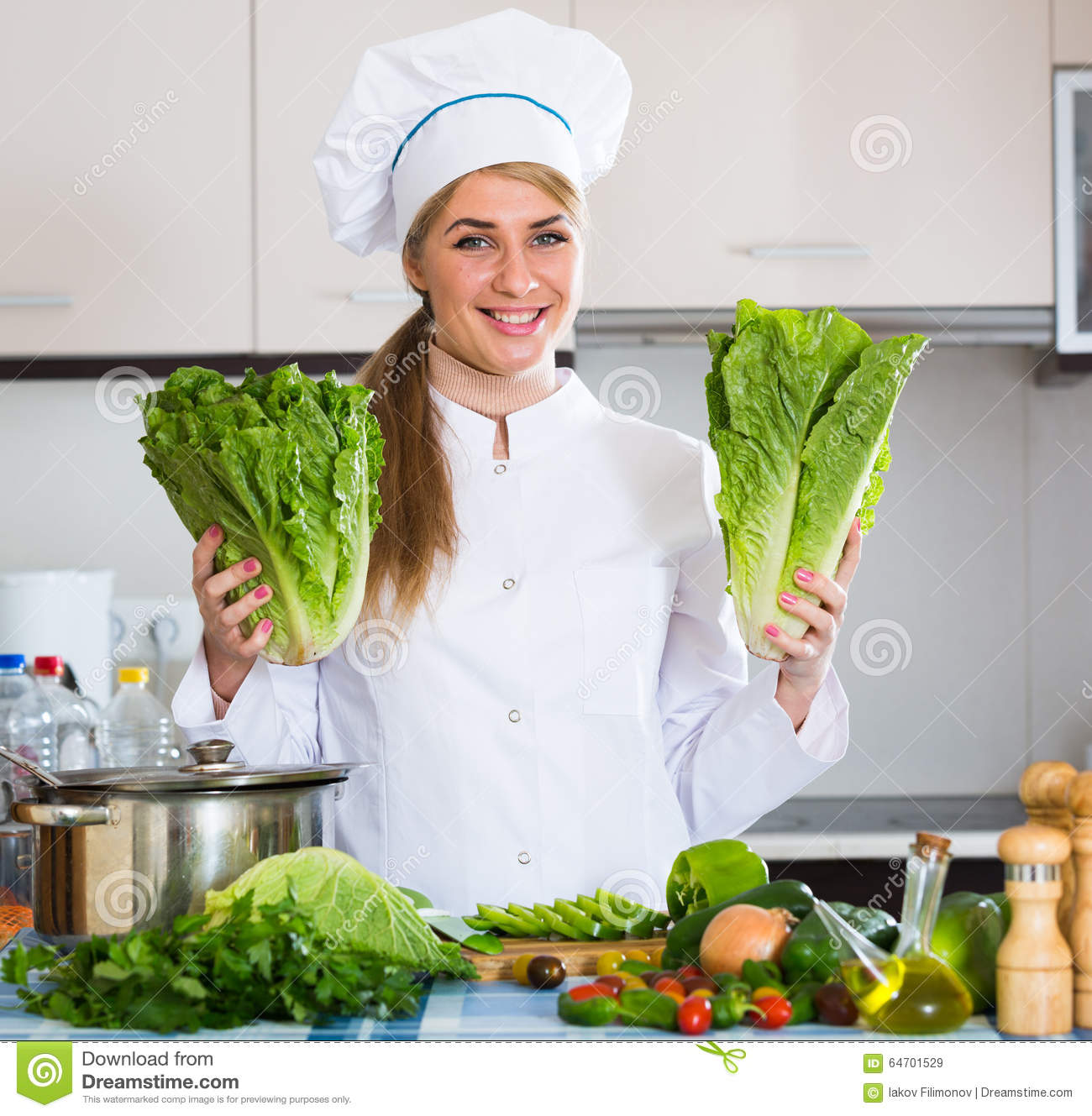Young chef with fresh lettuce posing in kitchen stock for Fresh chef kitchen