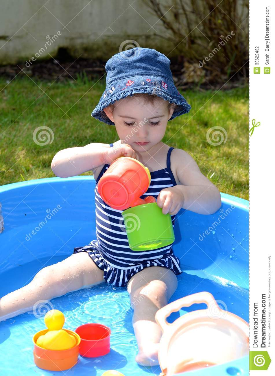 Young child with hat on playing with water in a paddling for Best children s paddling pool