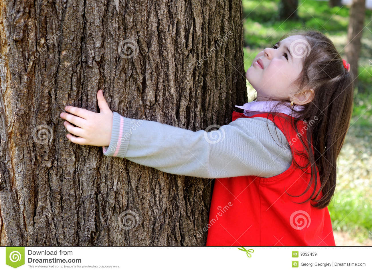 Young child hugging a tree.