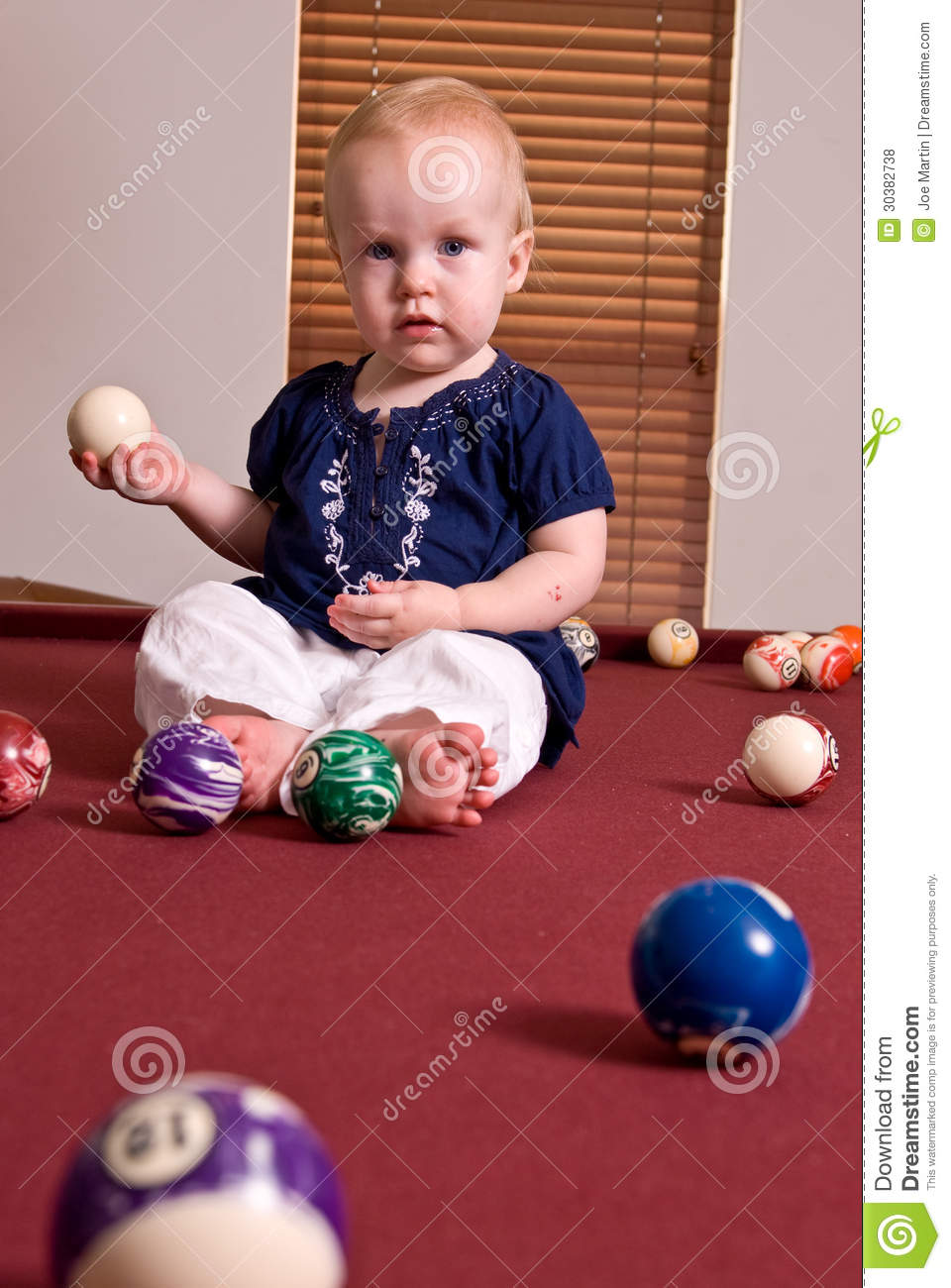 Young child sitting on a billiard table holding a cue ball