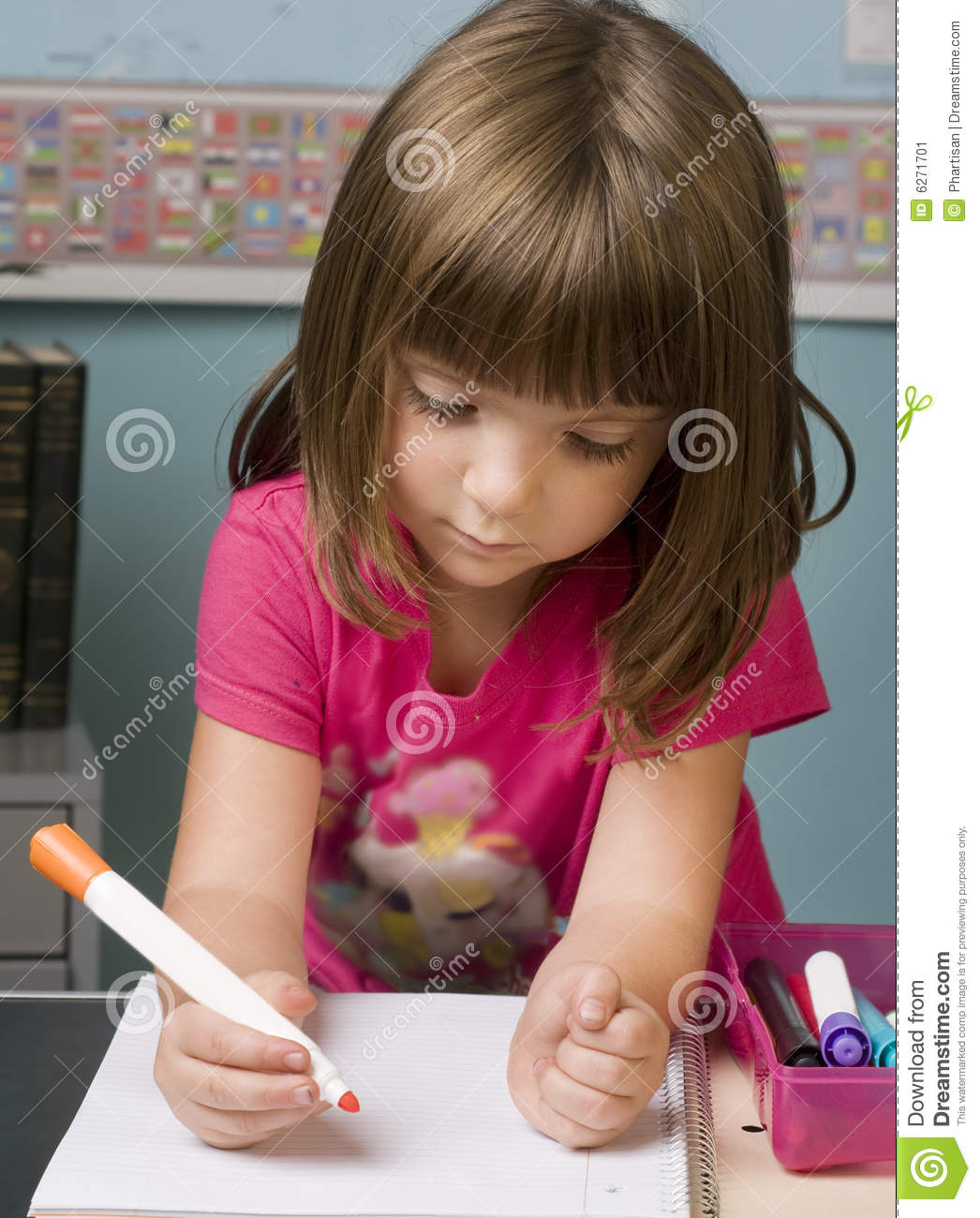 Young child working at her desk in class room