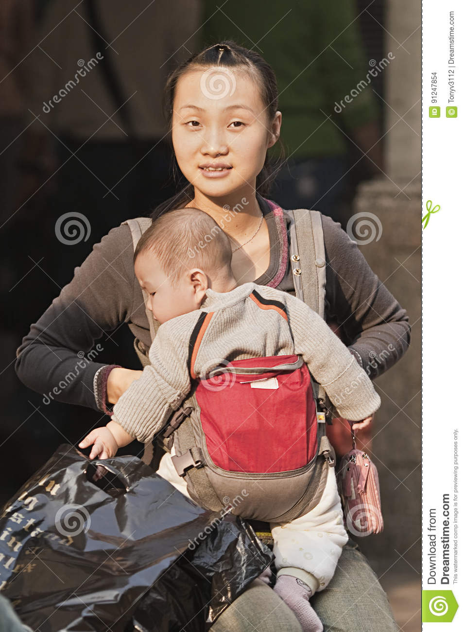 3edea38394d Young Chinese mother with baby in carry bag on July 1