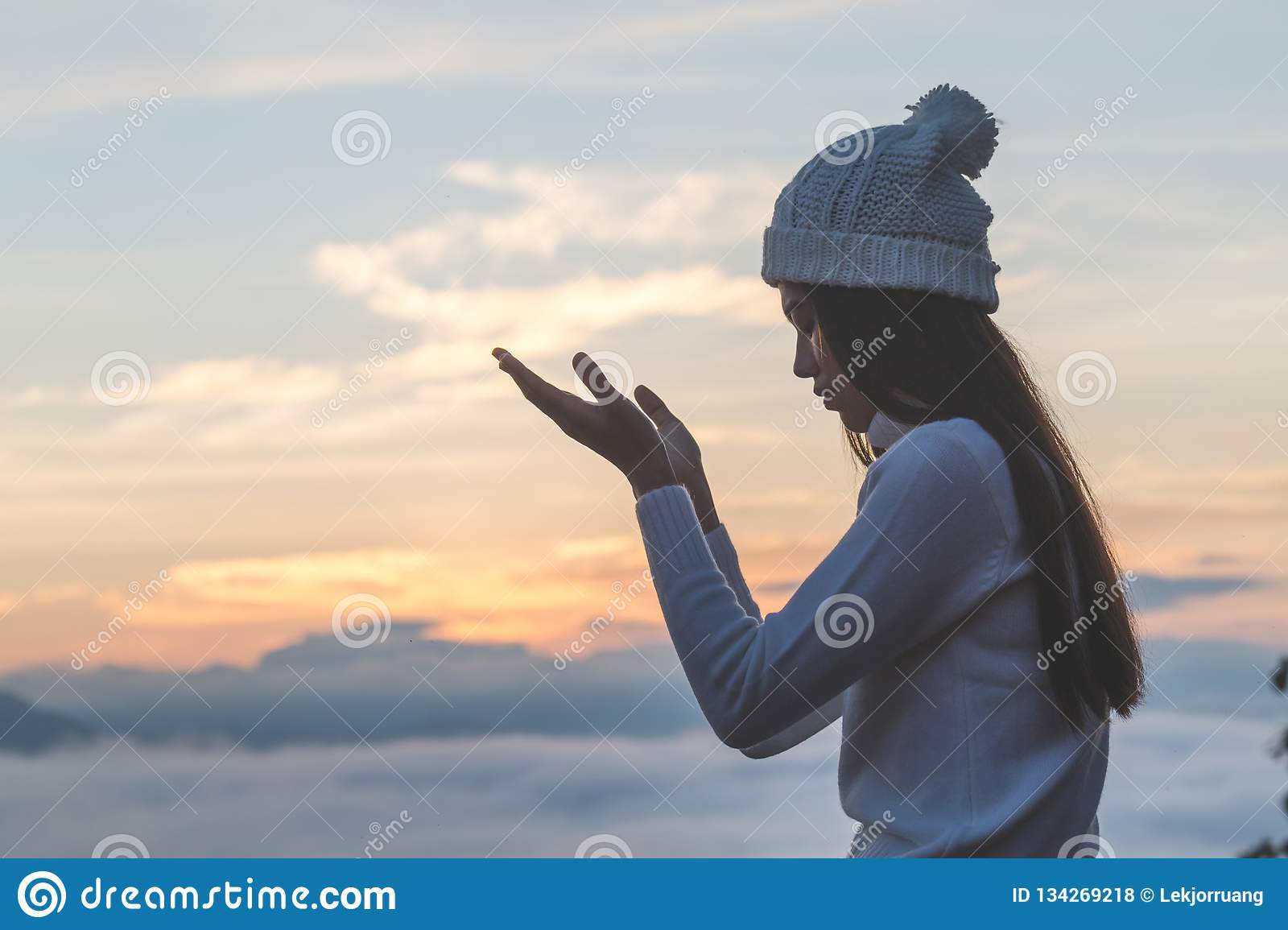 Young christian woman hands open palm up worship and praying to god at sunrise, Christian Religion concept background