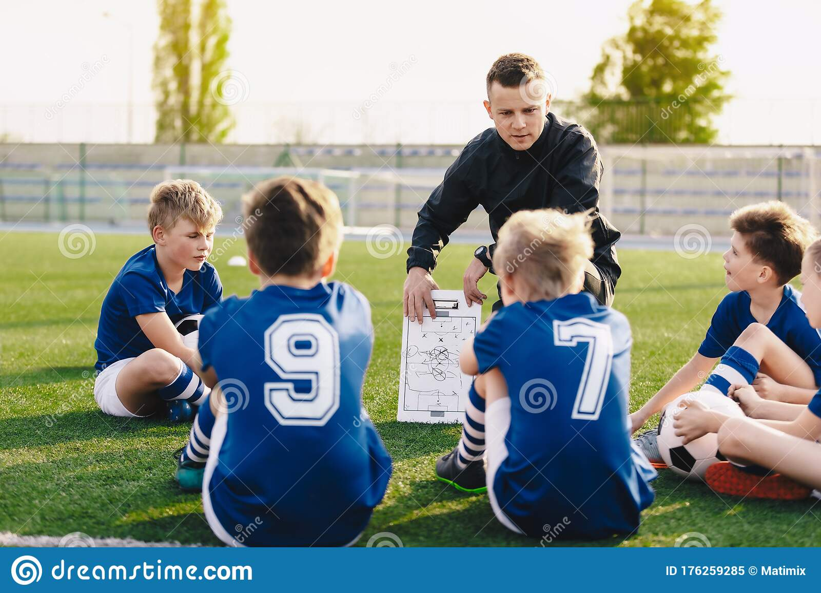 Young Coach Teaching Kids On Football Field. Football ...