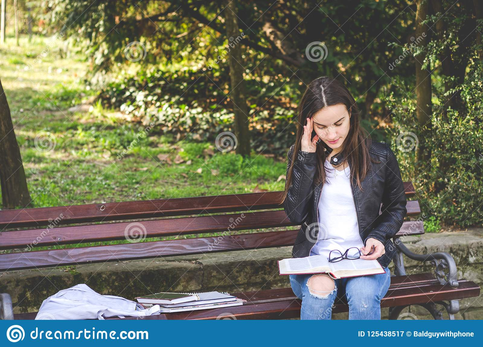 Young college or school girl feeling sick with strong headache pain or migraine attack while she sitting on the bench in the park