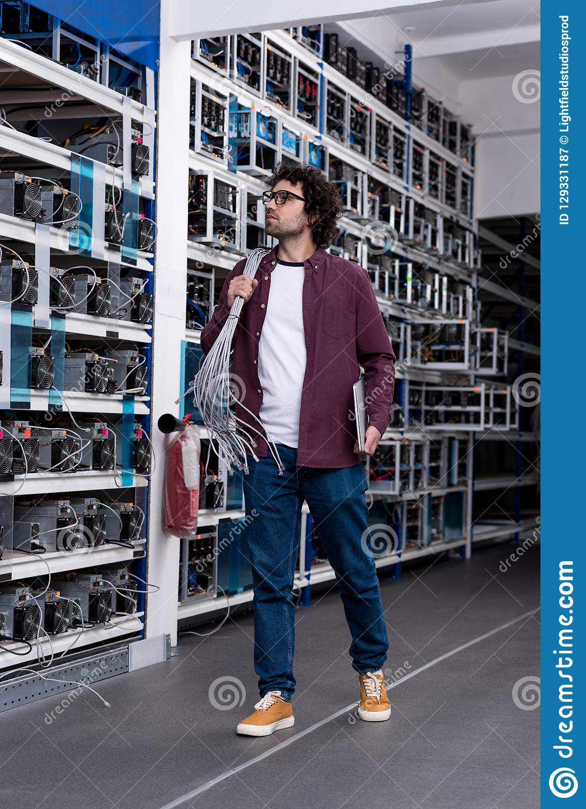 Young computer engineer with ethernet wires on shoulder at cryptocurrency mining farm royalty free stock photography