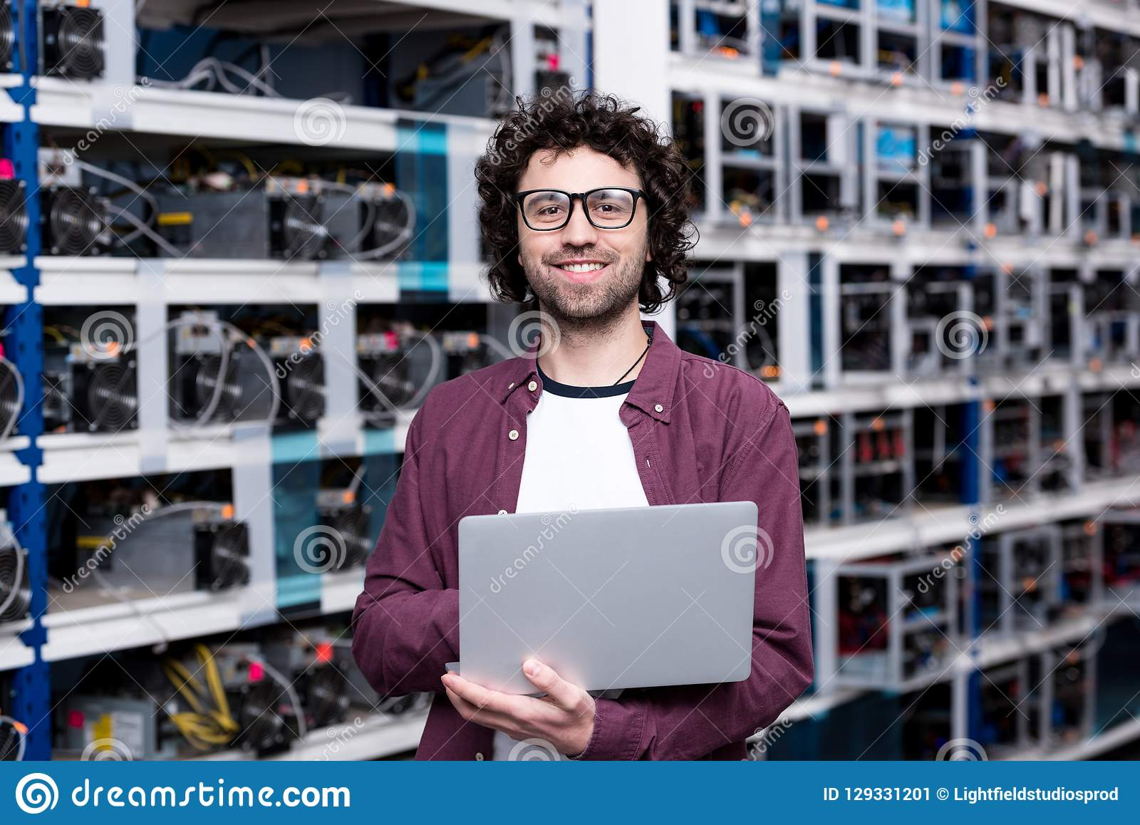 Young computer engineer with laptop at cryptocurrency mining farm stock image