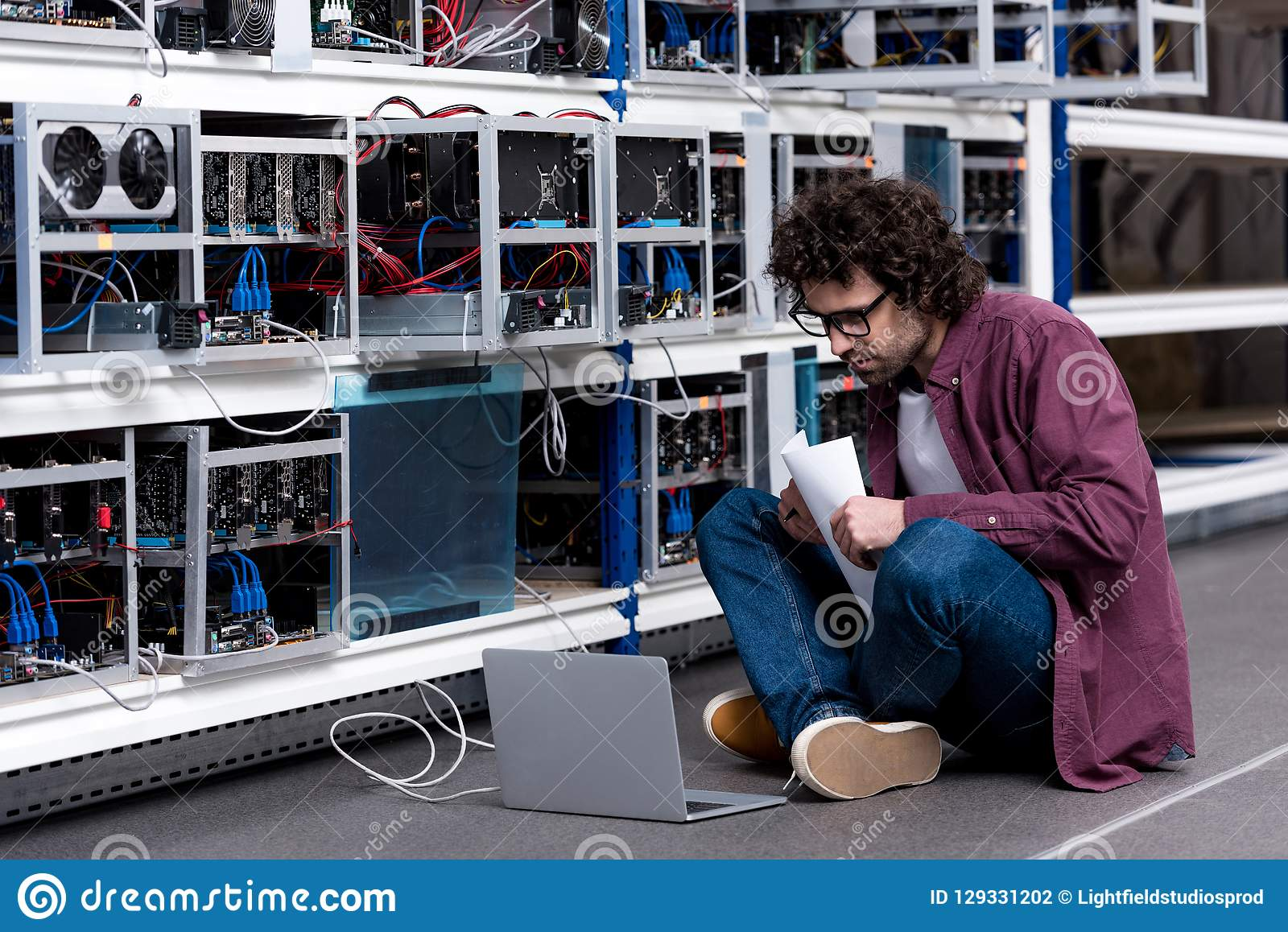 Young computer engineer working while sitting on floor at cryptocurrency mining farm stock photography