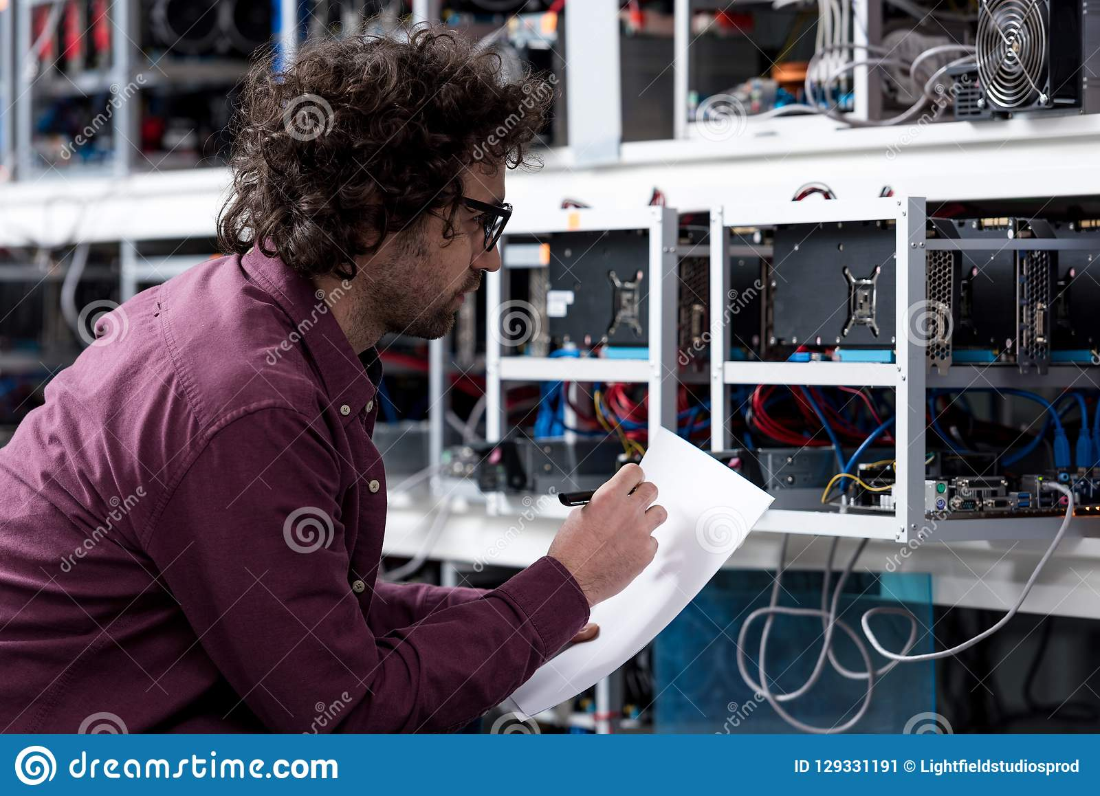 Young computer engineer writing on paper at cryptocurrency mining farm stock image