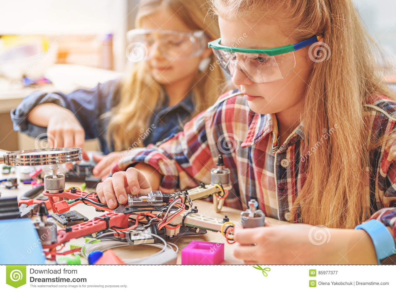 Young concentrated technicians working at drone