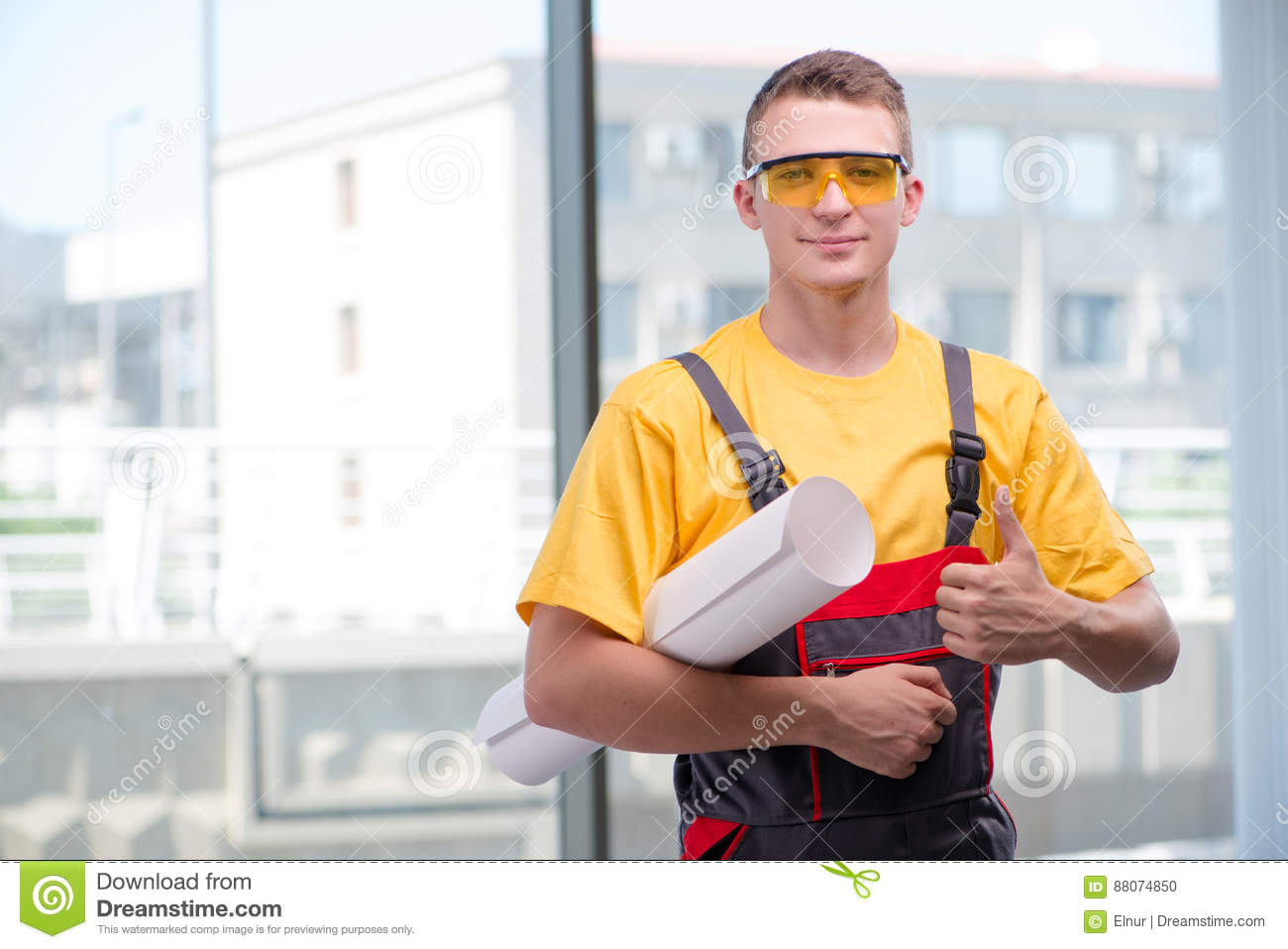 The young construction worker in yellow coveralls