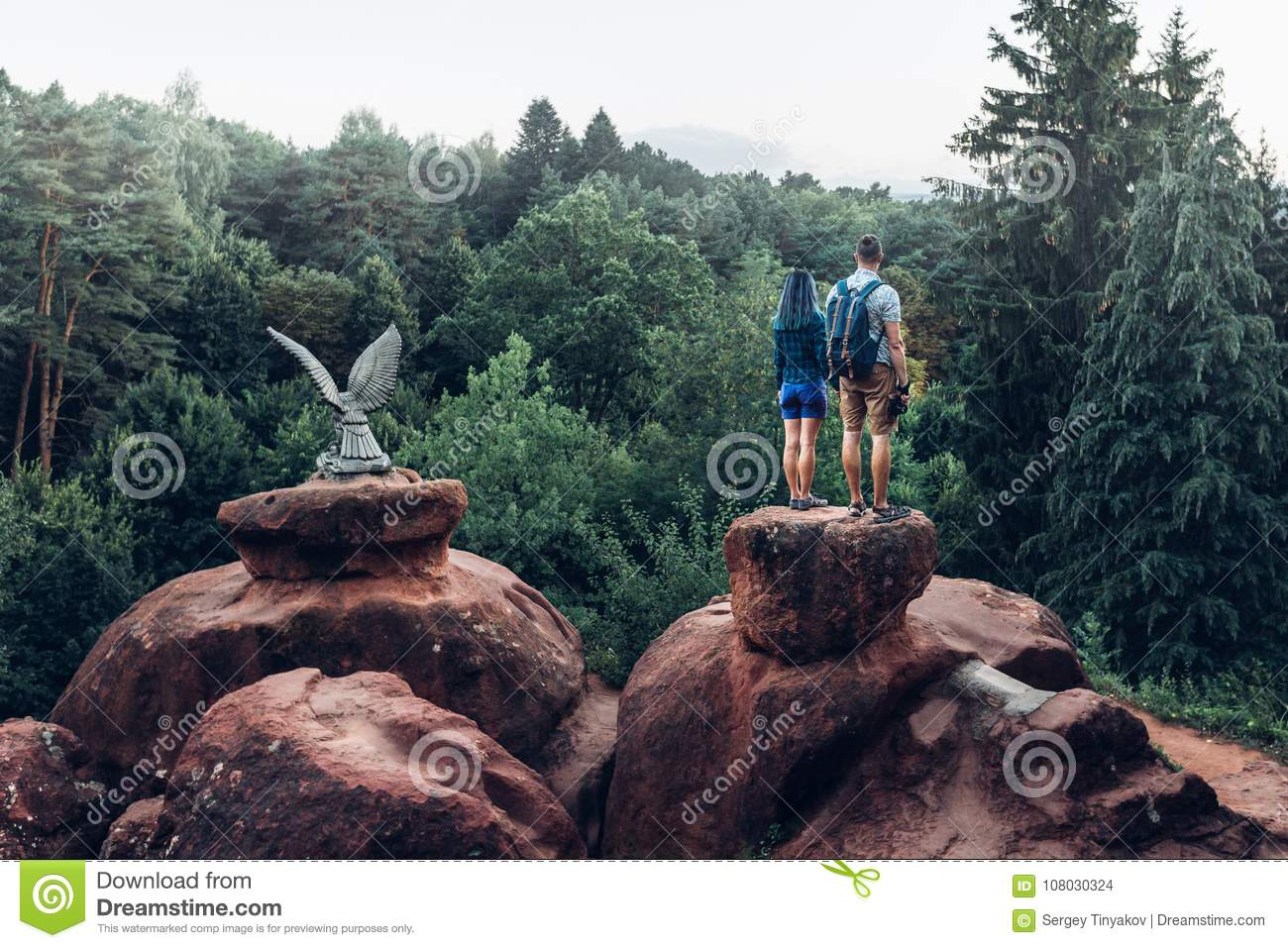Young Couple Of Backpackers Standing On Top Of Mountain And Enjoying View Of Nature In Summer