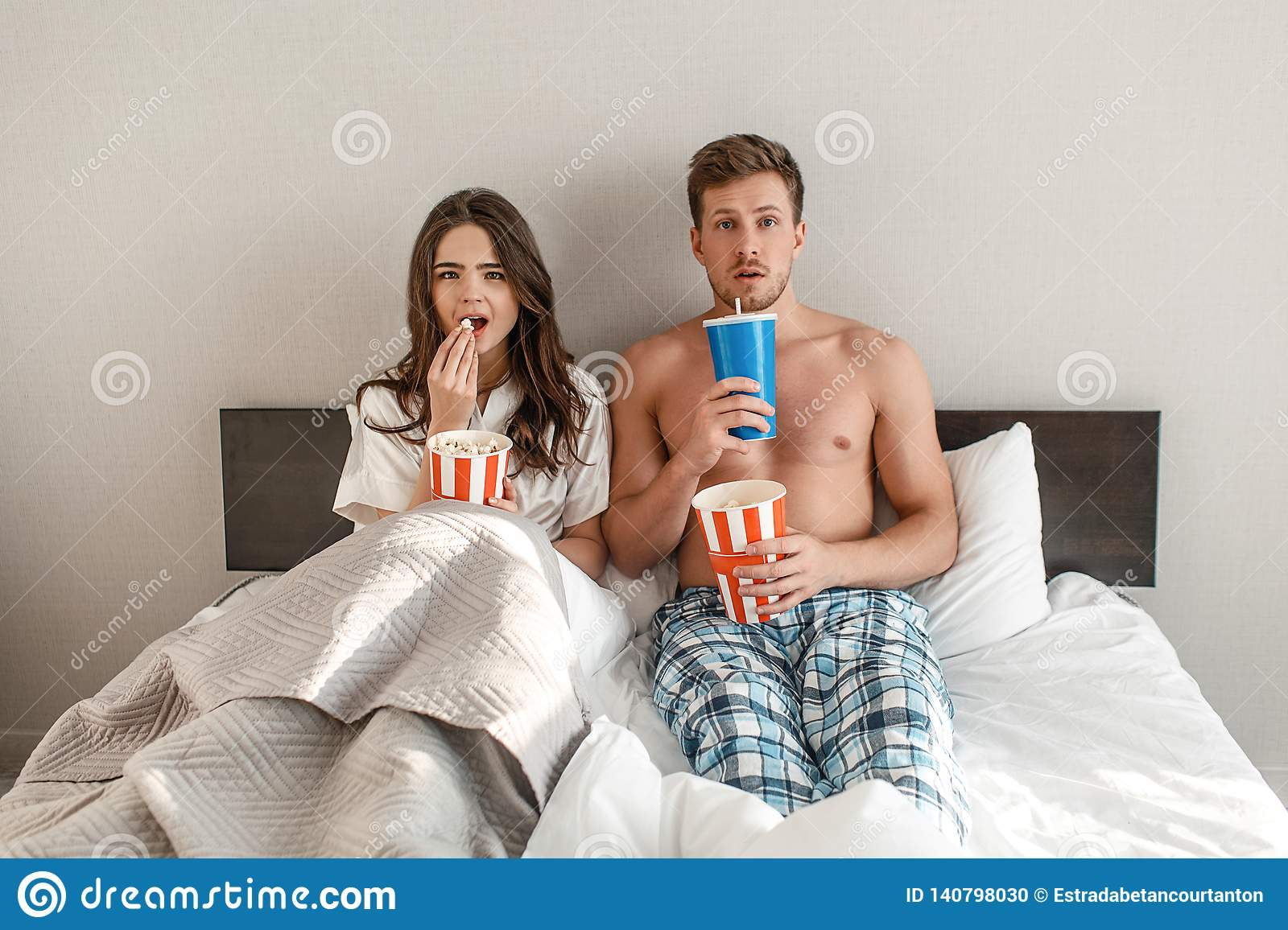 Young couple in the bed. An intrigued beautiful man and woman are eating popcorn and watching TV together in bedroom
