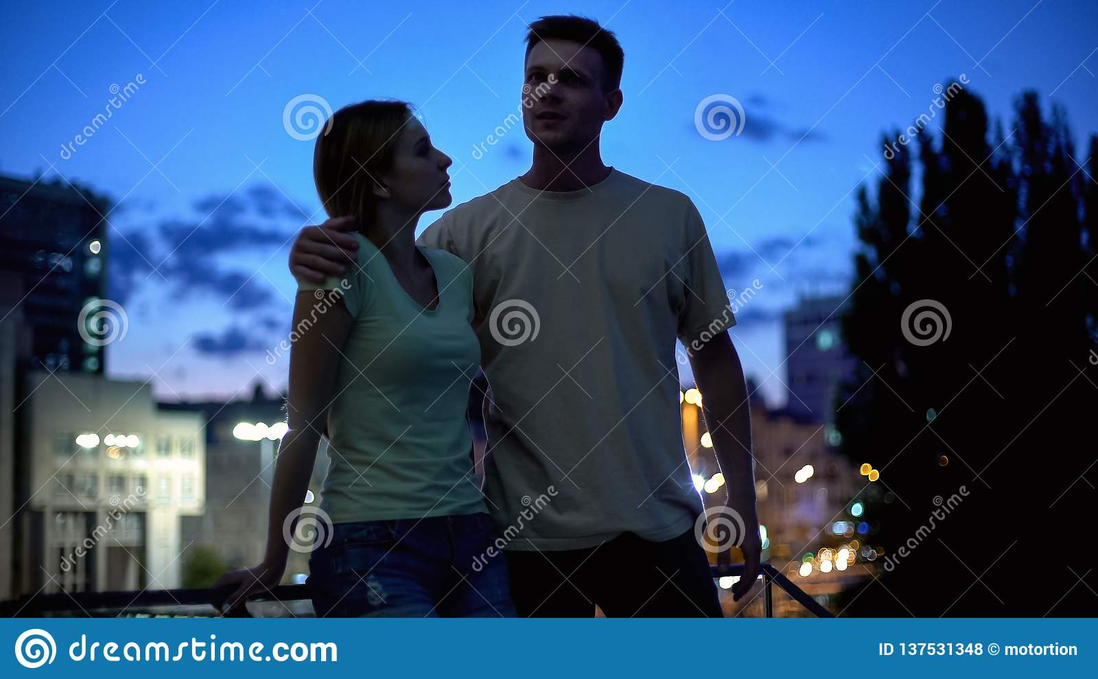 Young couple in casual clothes communicating, after-work walk in evening city